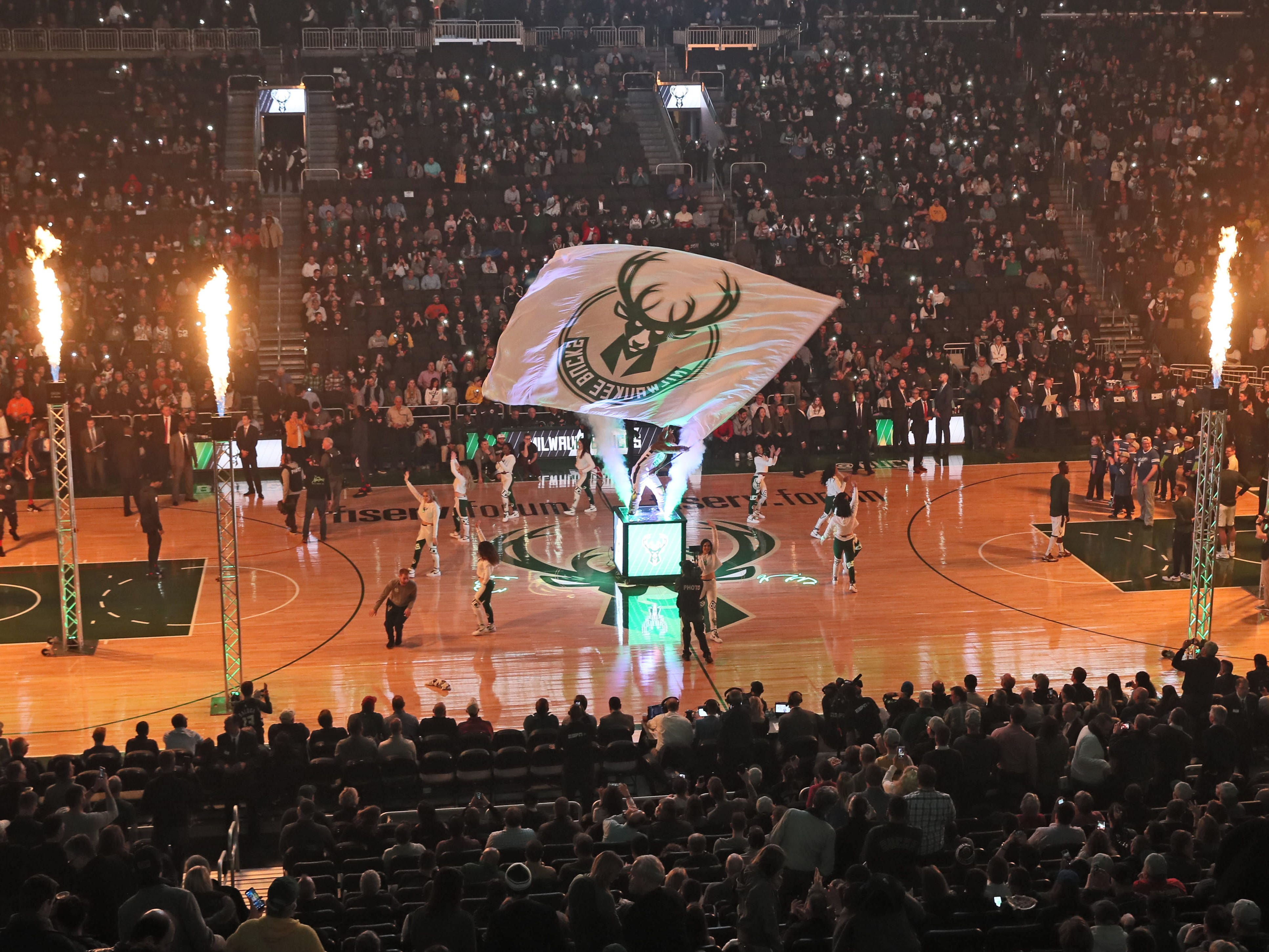 Bango, the Milwaukee Bucks mascot, waves the Bucks flag amid columns of flame as the players are introduced on Feb. 6. This is all part of the program that Johnny Watson has to keep moving smoothly.