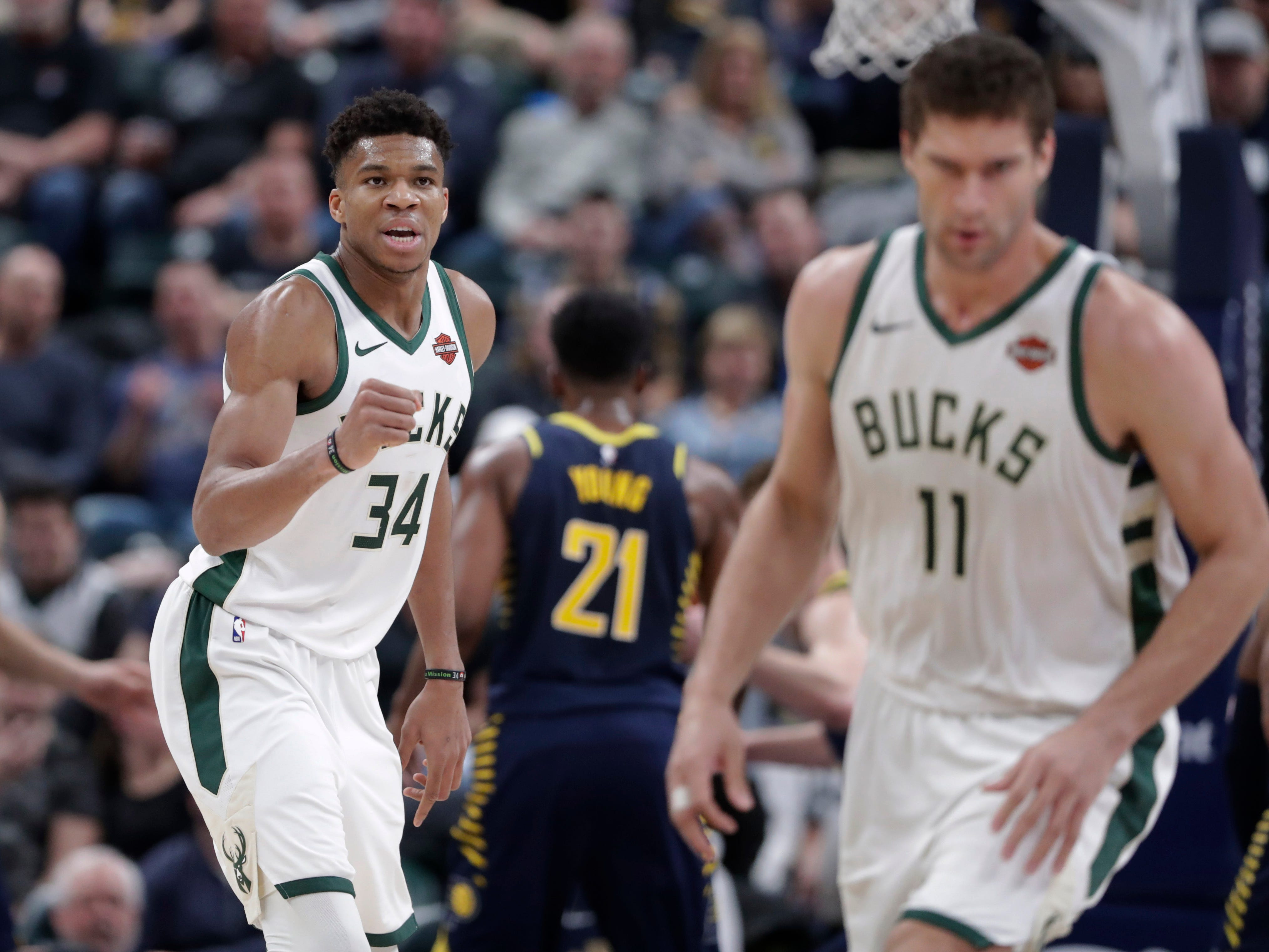 Giannis Antetokounmpo gives Brook Lopez an attaboy after he passed out to the Bucks center, who then proceeded to drain a three-pointer against the Pacers during the first half on Wednesday.