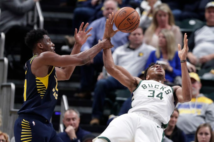 Bucks forward Giannis Antetokounmpo loses his balance as he's fouled by Pacers forward Thaddeus Young during the first half on Wednesday night in Indianapolis.