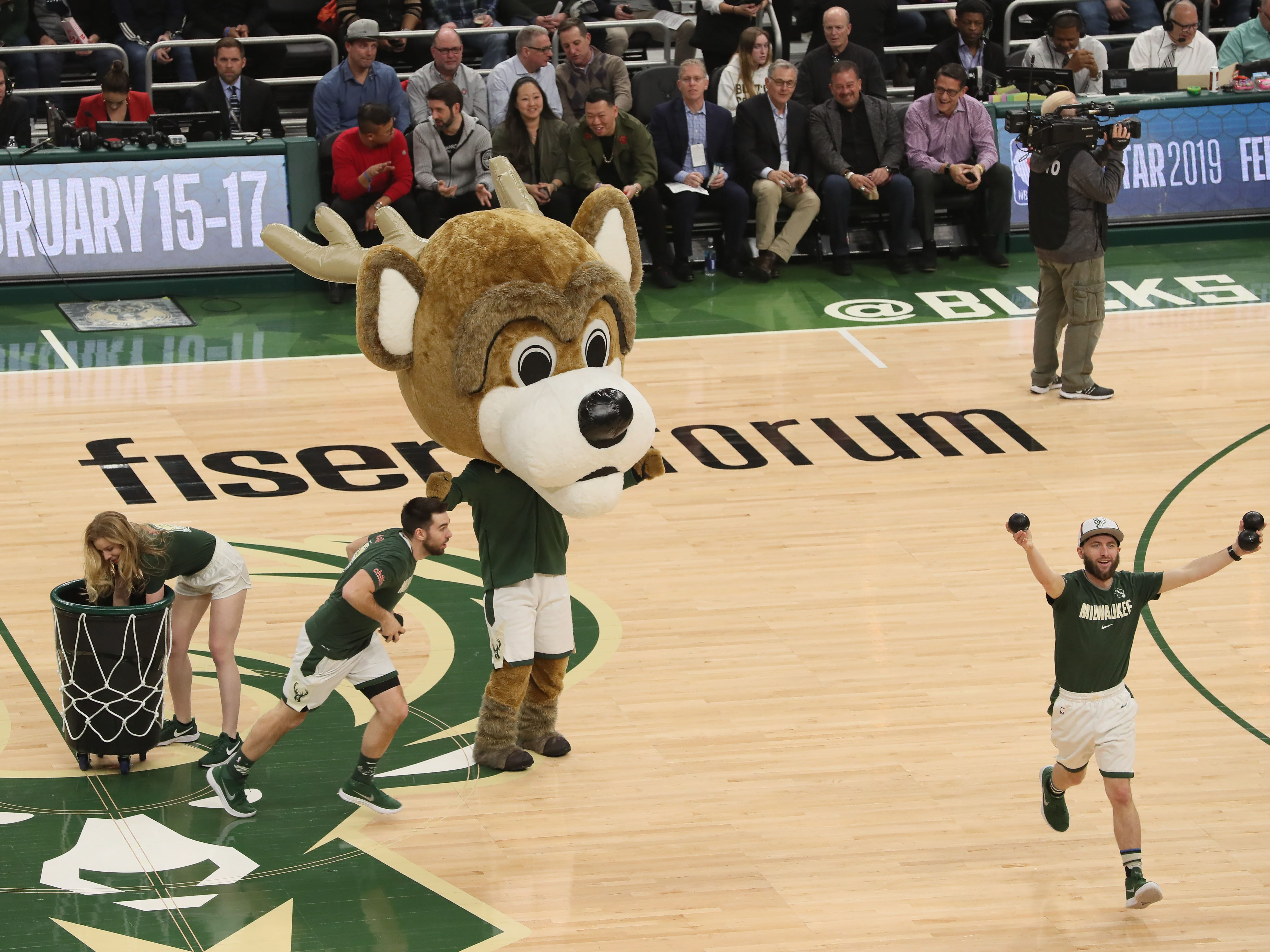 Bango, wearing an oversized head, leads the throwing of T-shirts into the crowd.