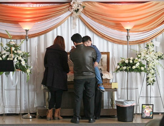 The family of Bill Thao stood next to his tiny casket at his visitation Jan. 2, 2015, at Lakeview Funeral Home, 9075 N. 76th St. Bill's father, Samboon Thao (right), holds Bill's little brother Magic Thao, 3. His wife, Suabna Xiong, is at left. Bill's grandmother is in front of them stroking the boys head in the casket.