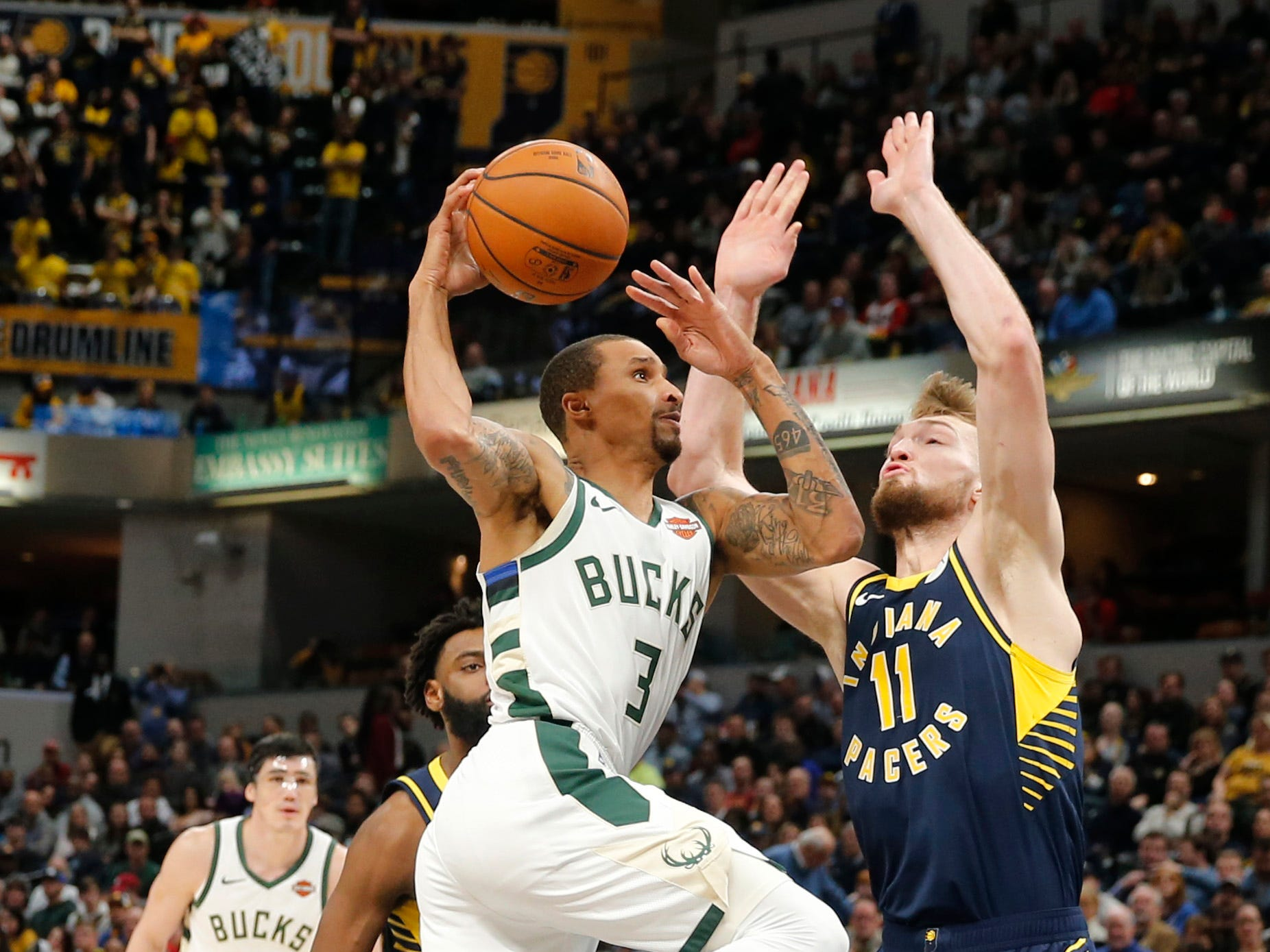 Bucks guard George Hill goes up for a shot against Pacers forward Domantas Sabonis after driving to the basket during the third quarter.
