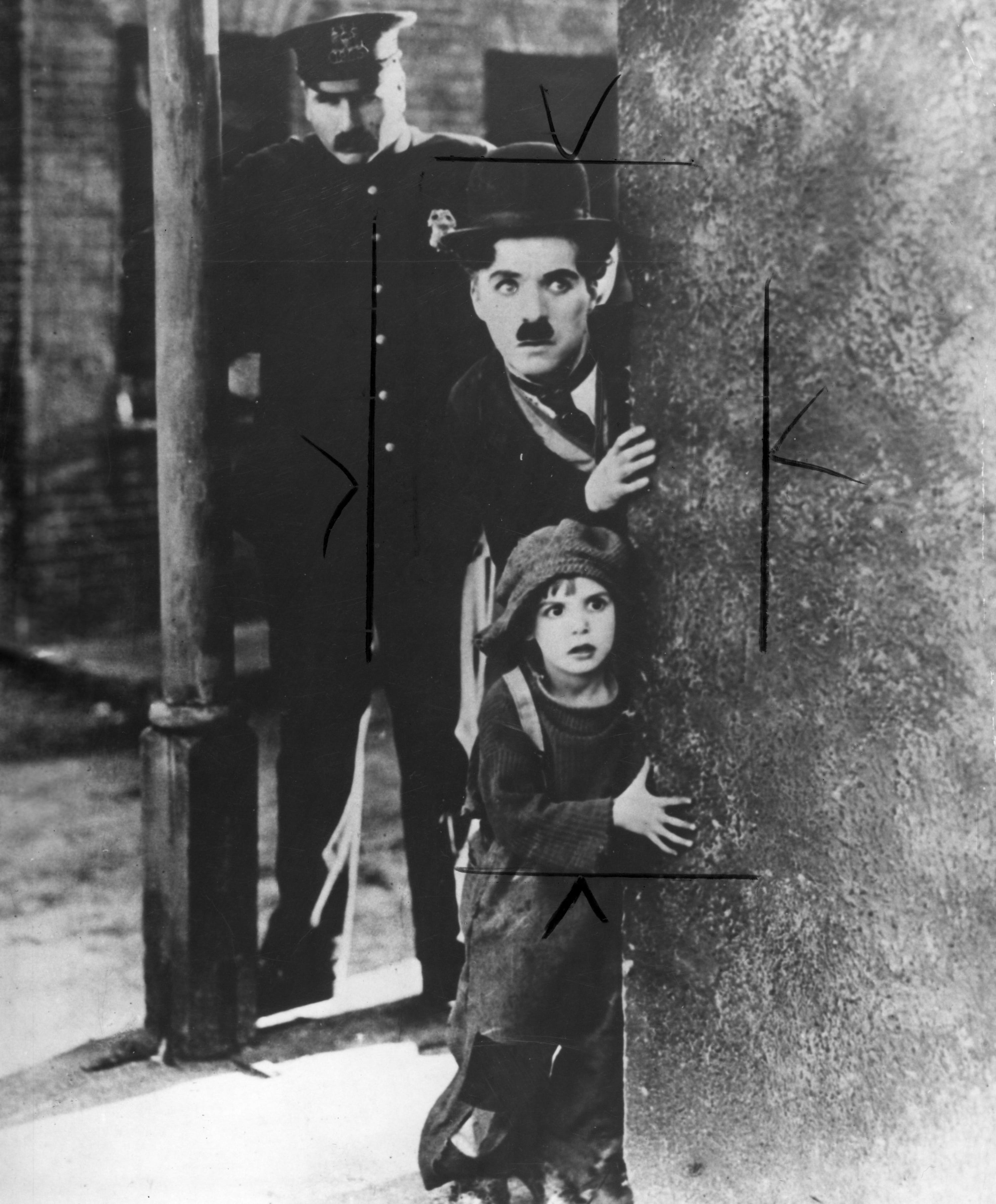 """Charlie Chaplin's Little Tramp (center) and the Kid (Jackie Coogan) attract unwanted attention in a scene from """"The Kid."""" The 1921 silent classic is showing at the 2019 Beloit International Film Festival."""