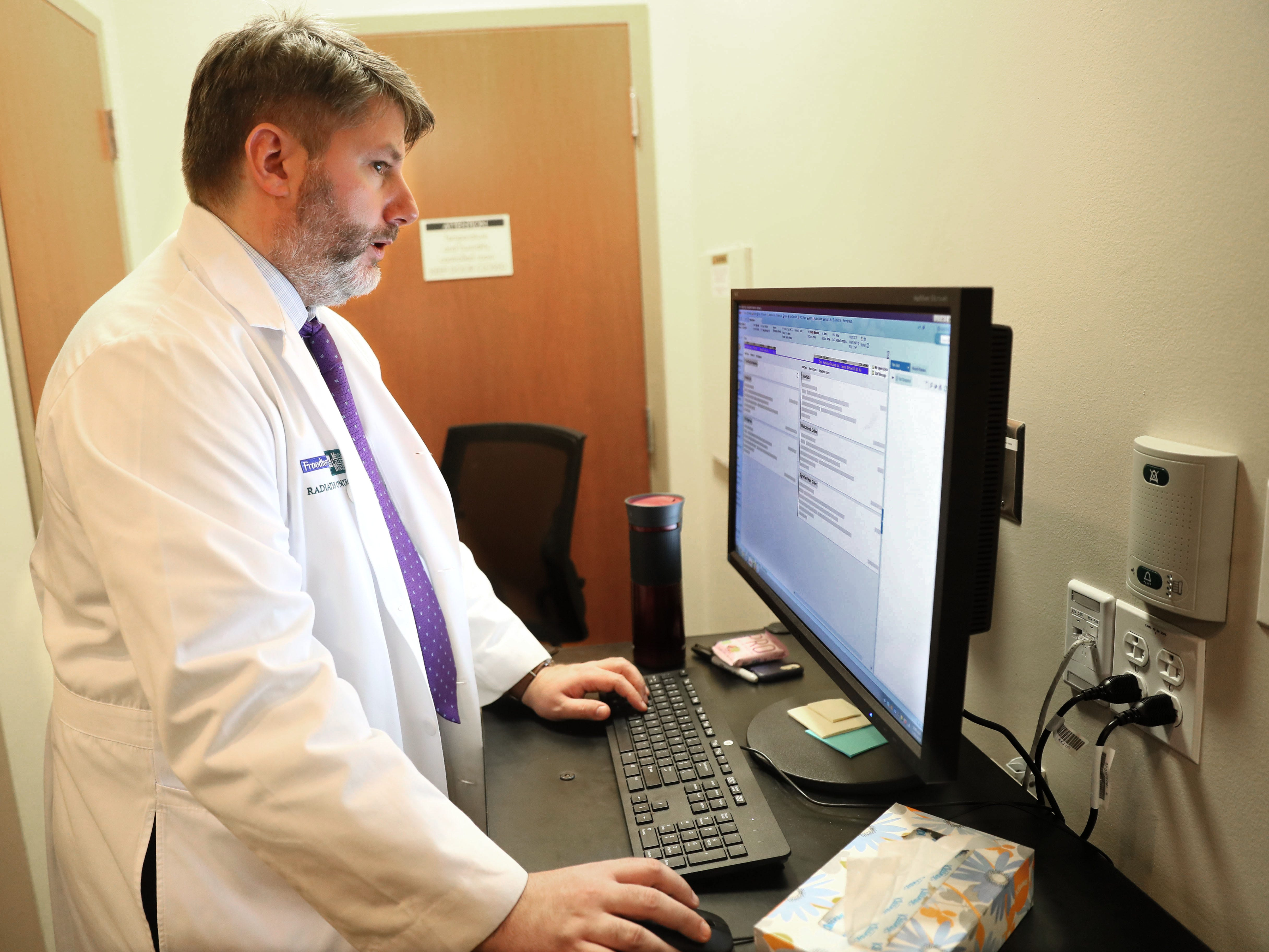 Michael Straza, Paula Wendt's oncologist, looks over patient data before the treatment.