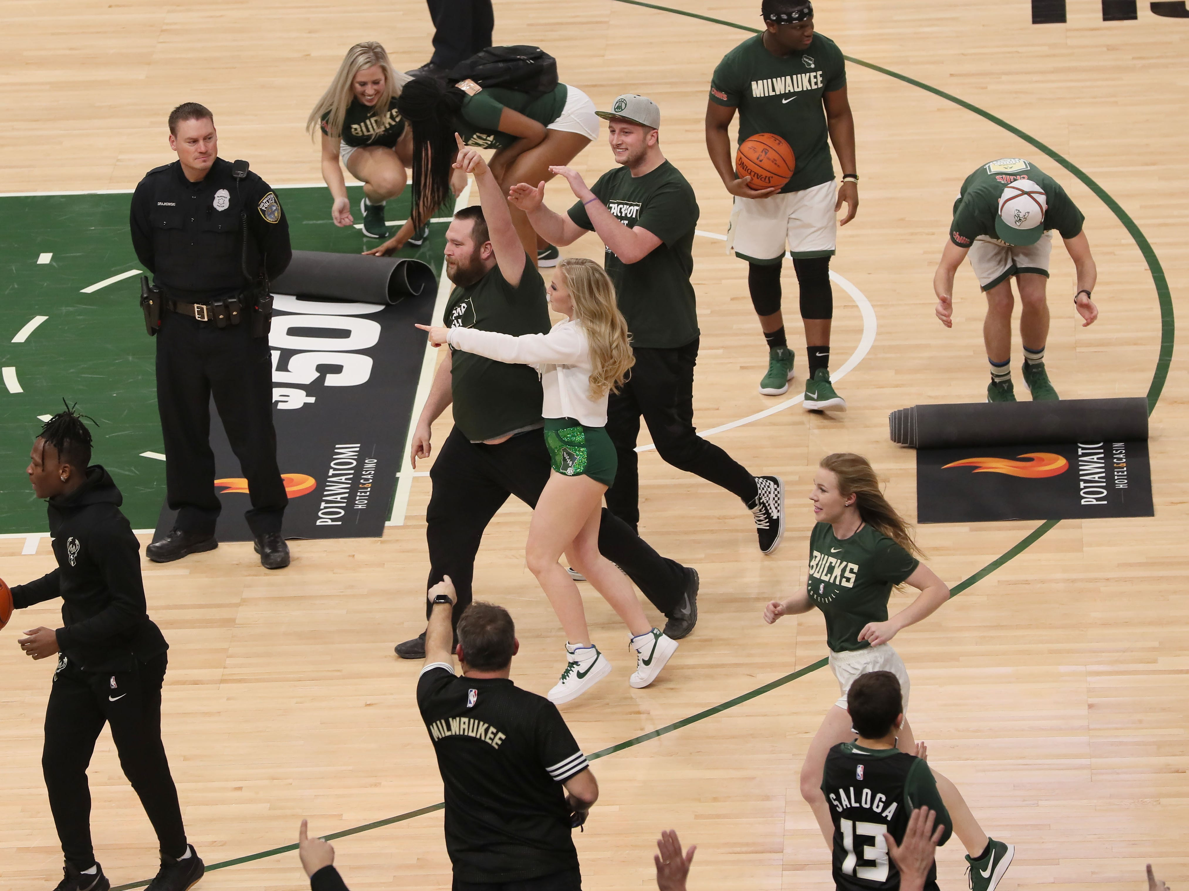 Surrounded by members of the Milwaukee Bucks Dancers, a jubilant Jimmy Appleton raises his finger after sinking a half-court shot and winning $5,000  in the Potawatomi Hotel & Casino Jackpot Shot contest during the game Feb. 6.