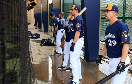 Milwaukee Brewers players wait their turn at the batting cage due to the rain-soaked fields on Thursday in Phoenix, Arizona.