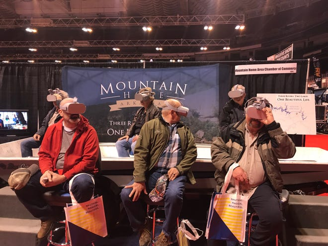Attendees at the Progressive St. Louis Boat and Sport Show watch a short virtual reality film about the Twin Lakes Area. The VR display is the centerpiece of the Mountain Home Chamber of Commerce's booth display.