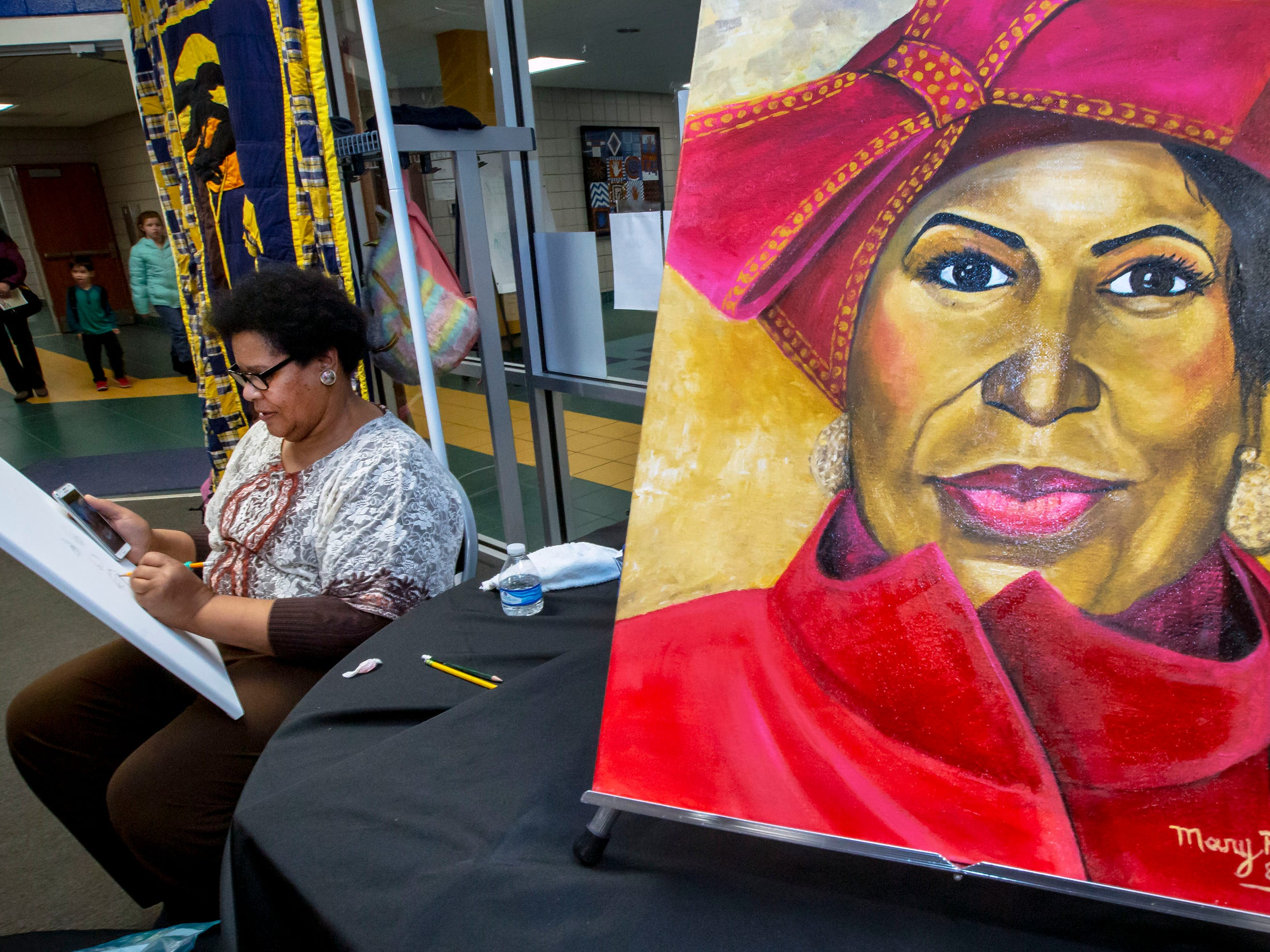 Mary Watkins works on a new painting at her booth at the African-American Cultural Celebration held at Patterson Park Community Center.