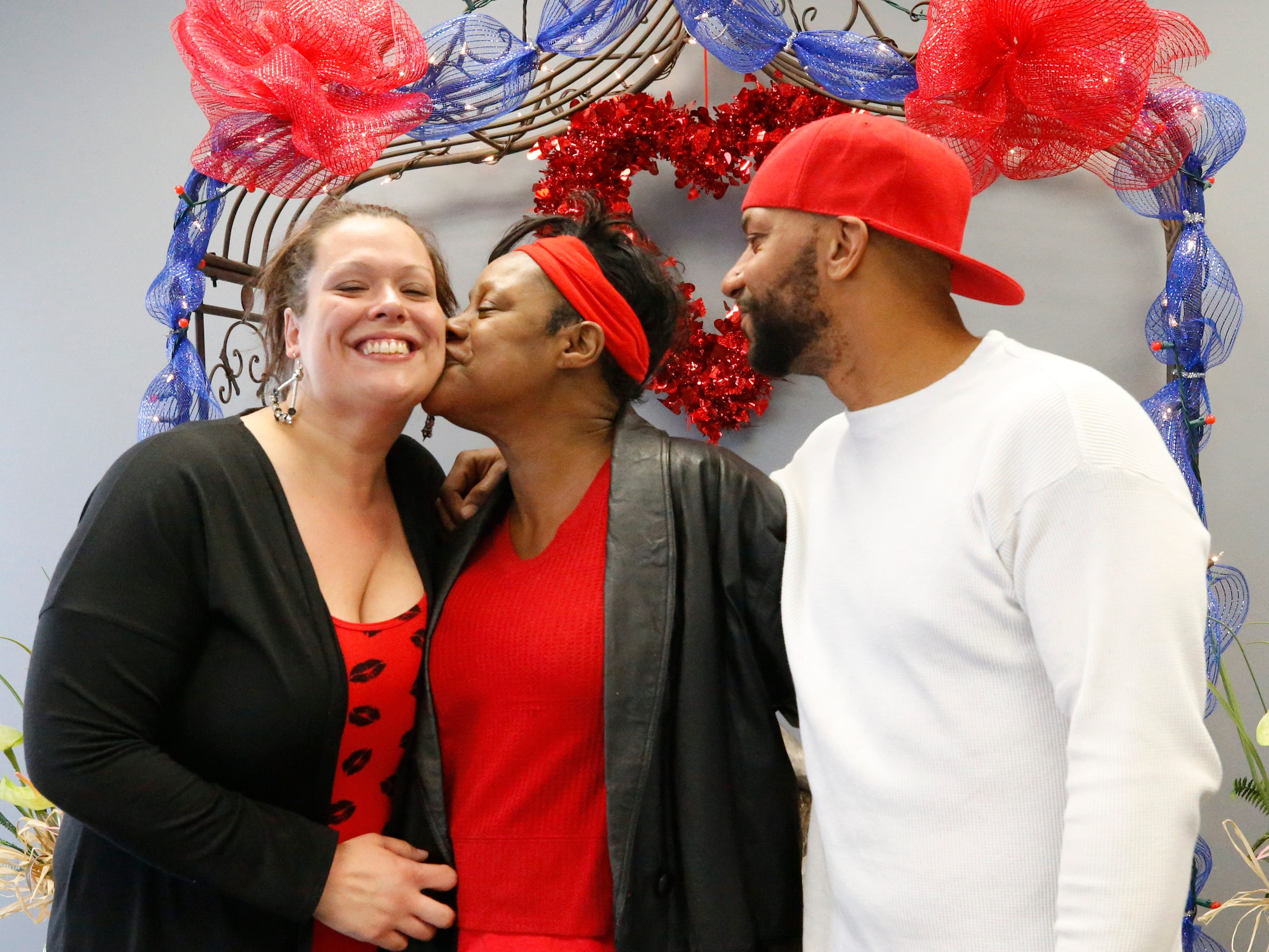 Vira King, middle, kisses Kimberly (Ervin) Aiden, left, after Aiden married her nephew Shermaine Aiden, right on Valentine's Day, in Murfreesboro, on Thursday, Feb. 14, 2019.