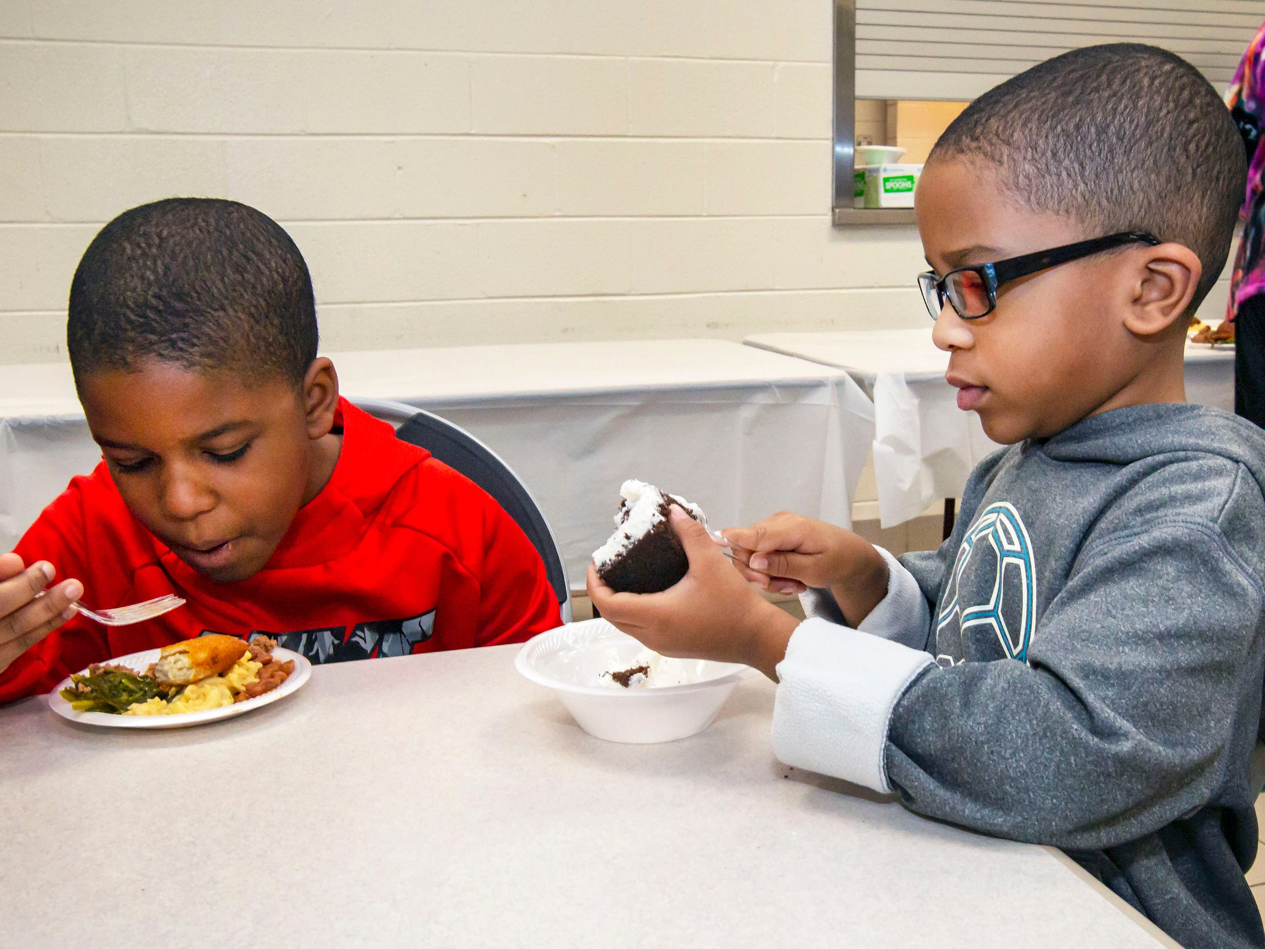Athan Green and Amari Green sample some soul food at the African-American Cultural Celebration held at Patterson Park Community Center.