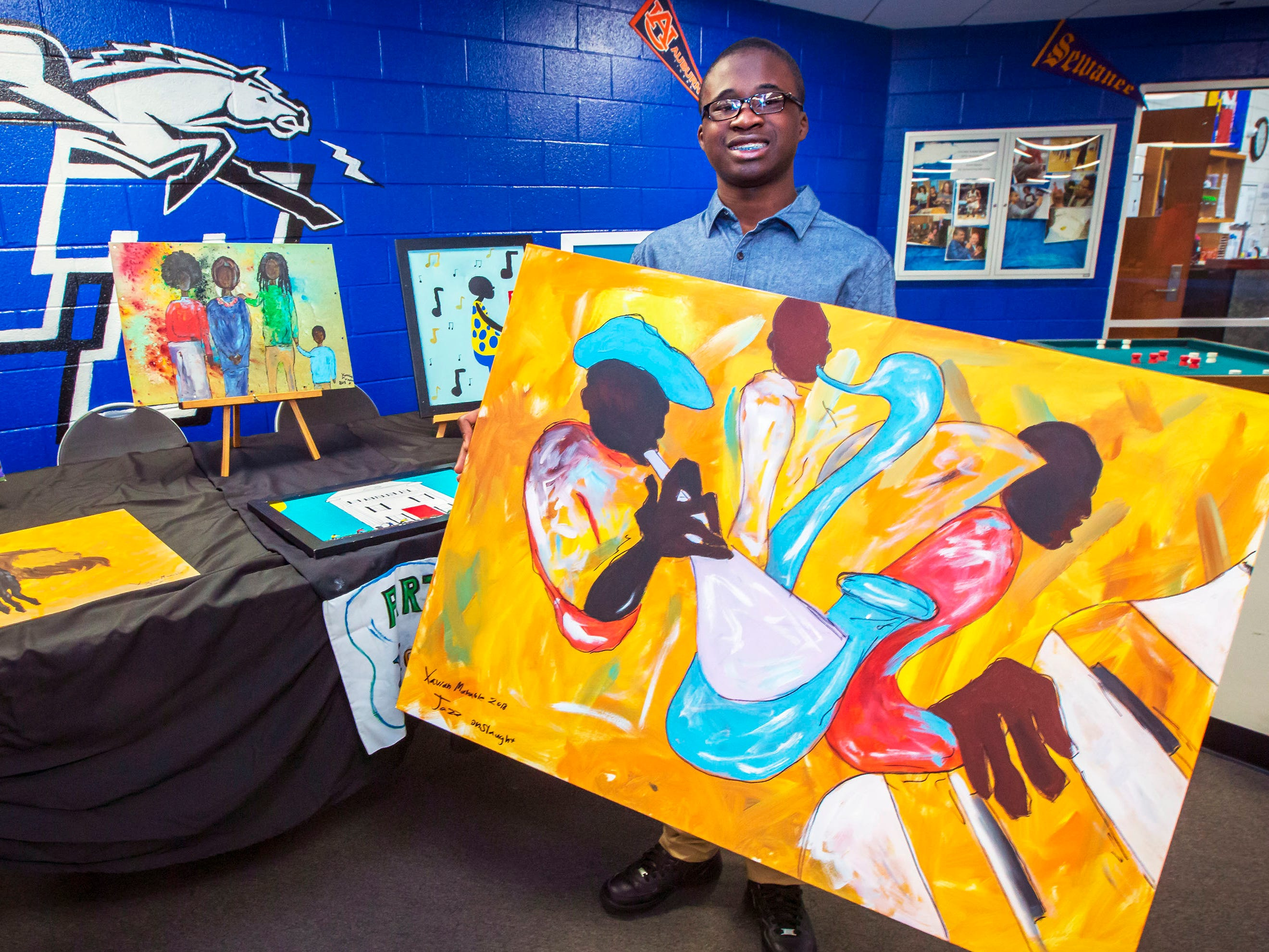 Xavian Marable holds one of his paintings at his booth at the African-American Cultural Celebration held at Patterson Park Community Center.