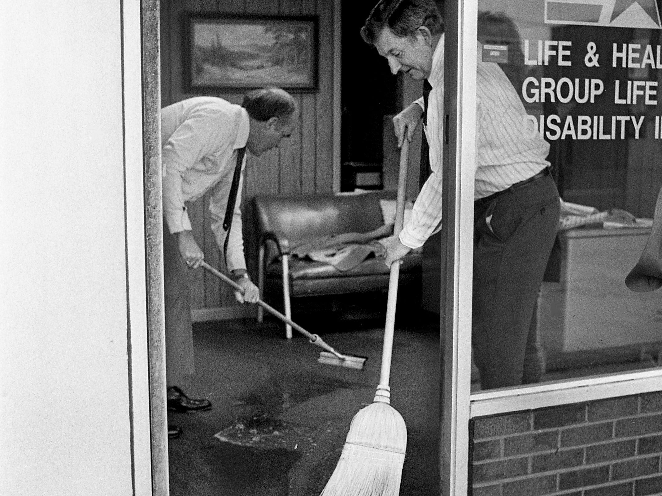 Wayne Beadle and Perry Carlton of the Life of Georgia Insurance Co. begin cleaning up after the water that filled the Lebanon town square receded Feb. 14, 1989. As much as 3 feet of water flooded the town square.