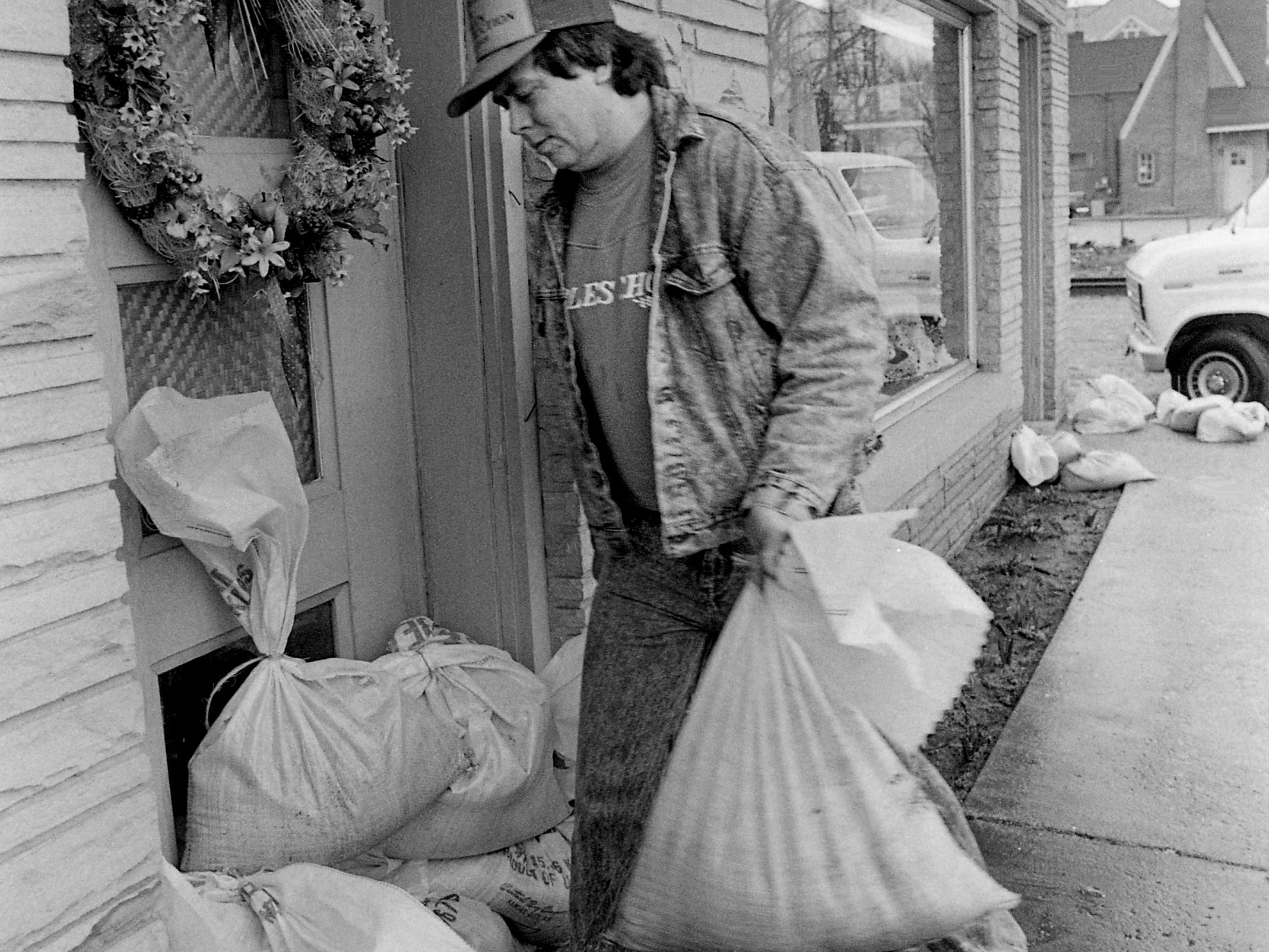 Lebanon businessman Jimmy Draper drops sand bags outside his mother's flower shop at 204 W. Main St. on Feb. 20, 1989, as more heavy rains were expected.