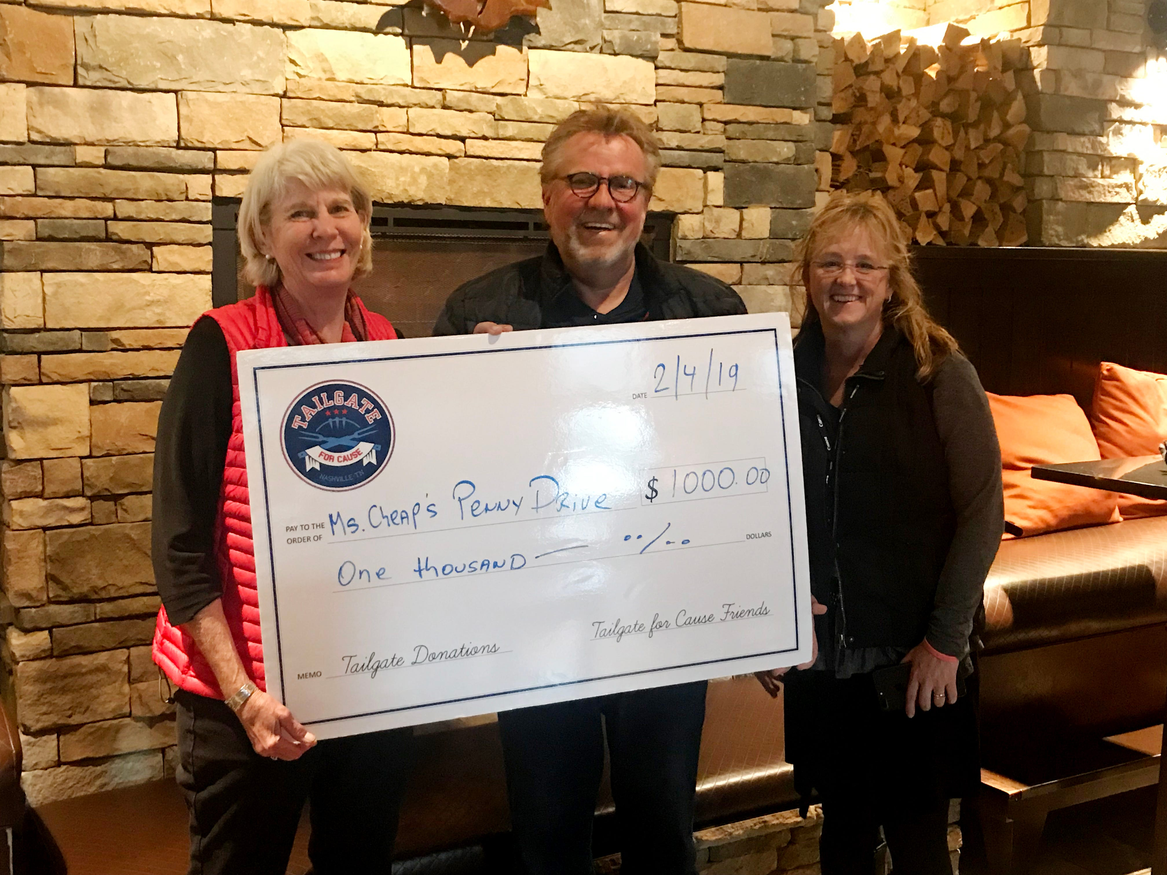 Tailgate for Cause founder Michael Gangwisch and V. Alexander's Claudia Richardson present a big check to Ms. Cheap.