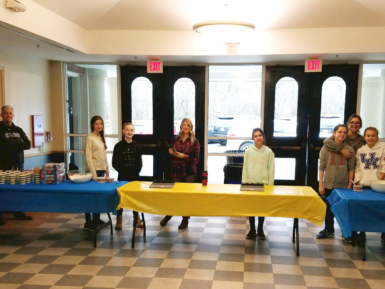 """Hot Chocolate Stand - """"Have Hot Cocoa & Smile""""...They COLLECTED $241.50. From left to right: Dr. Jeff Horner (Rachel's dad), Rachel Horner, Addison Irvin, Mrs. Niki Horner (Rachel's mom), Zoe Hawkersmith, Mia Hawkersmith, Mrs. Vale Hawkersmith (Zoe and Mia's mom), and Ann Gentry Lambert."""
