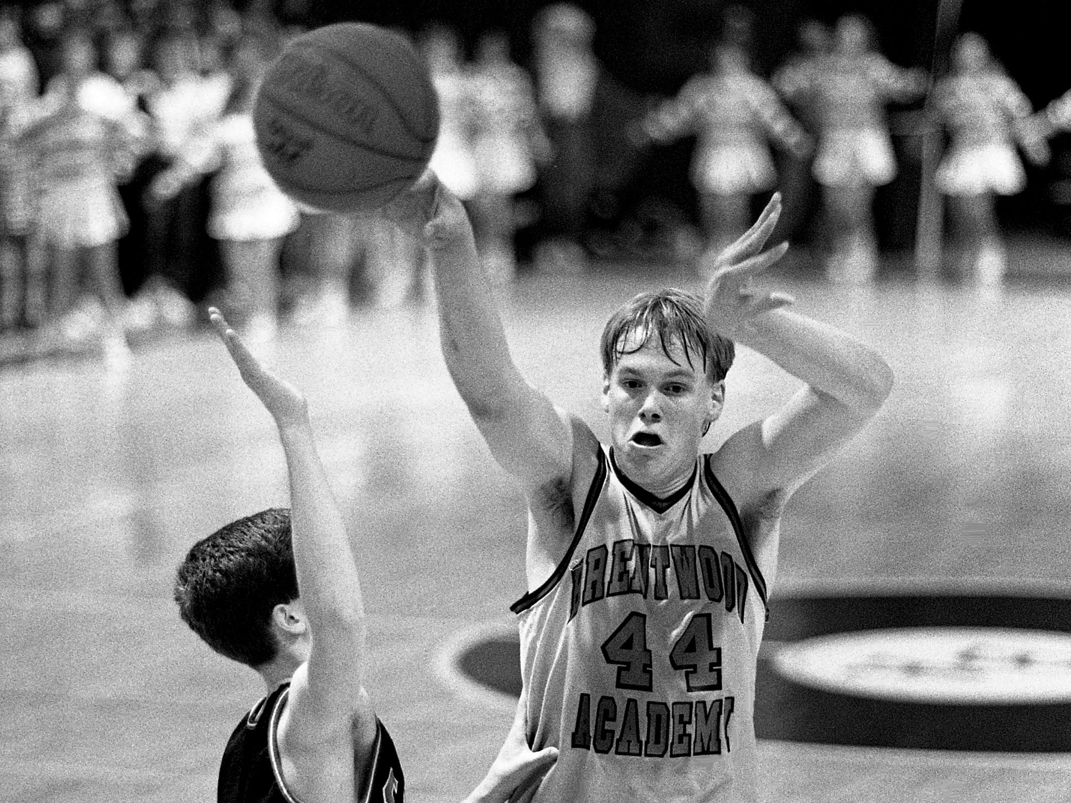 Brentwood Academy's Shawn Wilson (44) passes inside to a teammate while guarded by Klane Maples of Cookeville High on Feb. 17, 1989. The host Brentwood of Class AA showed its muscle against Class AAA opposition, beating No. 7-ranked Cookeville for the second time this season.
