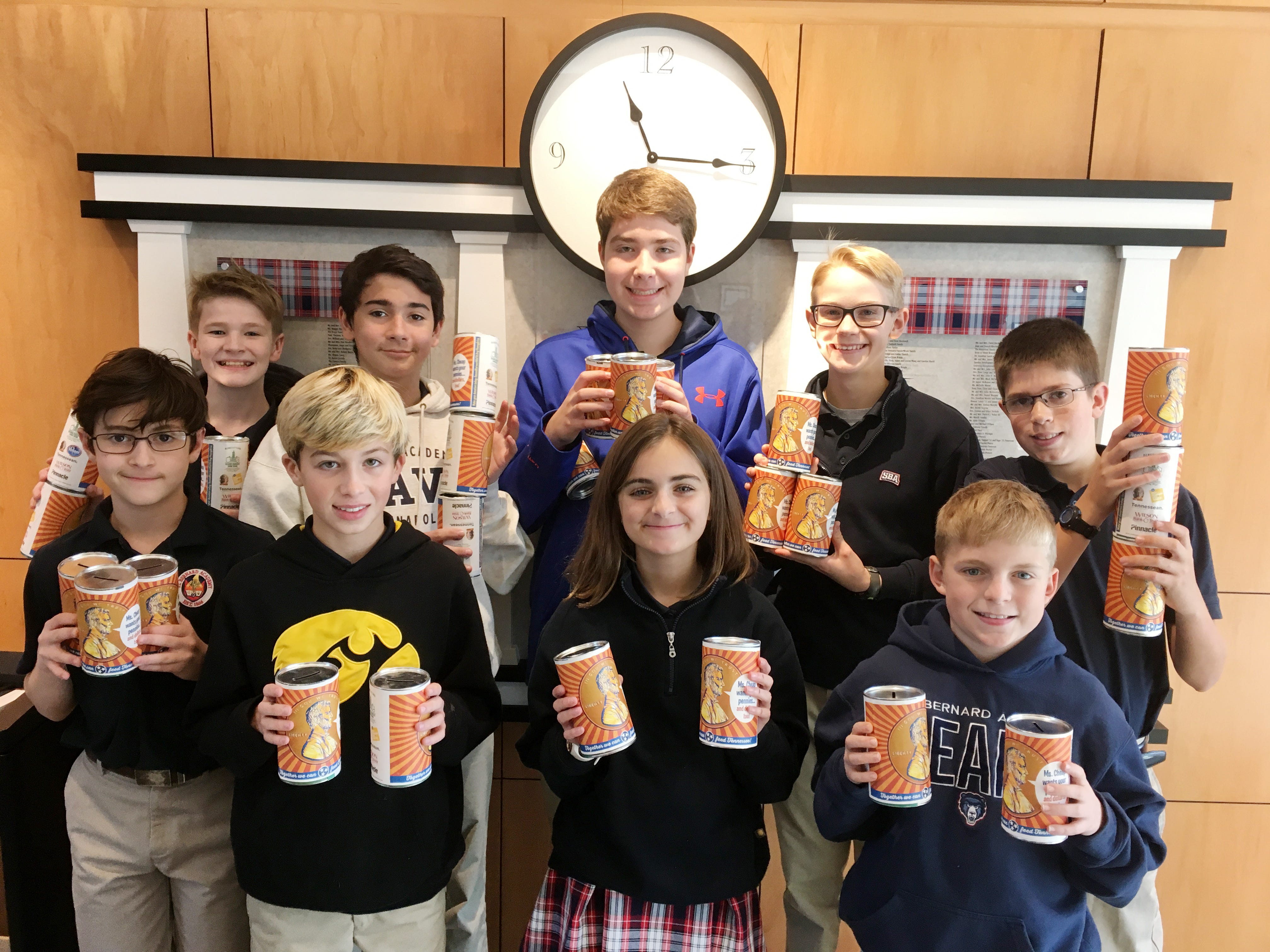 St. Bernard Academy students show off their Penny Drive cans. Eighth-grader Alec Jacobs (in blue in the middle) organized the drive for his school.