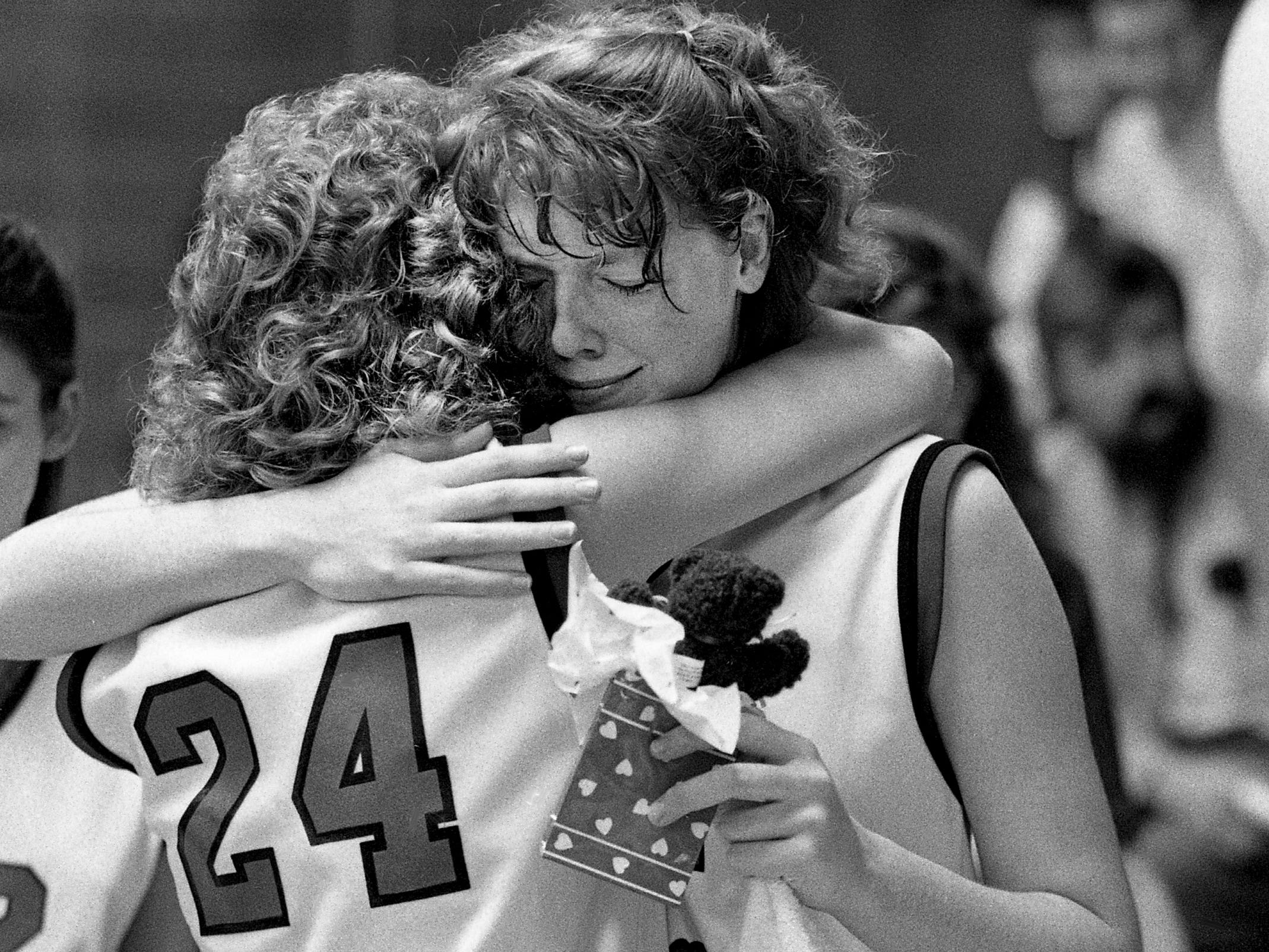 St. Bernard Academy senior Carol Villa (24) and junior Melinda Laake hug after their final game Feb. 14, 1989, as the school will close its doors forever this spring. St. Bernard lost to District 7-A foe Davidson Academy 42-36.