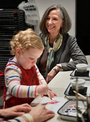 Two-year-old Elizabeth Woods paints in the expanded Martin ArtQuest at the Frist Art Museum as her mom, Molly, talks with Frist CEO Dr. Susan Edwards on Feb. 14.
