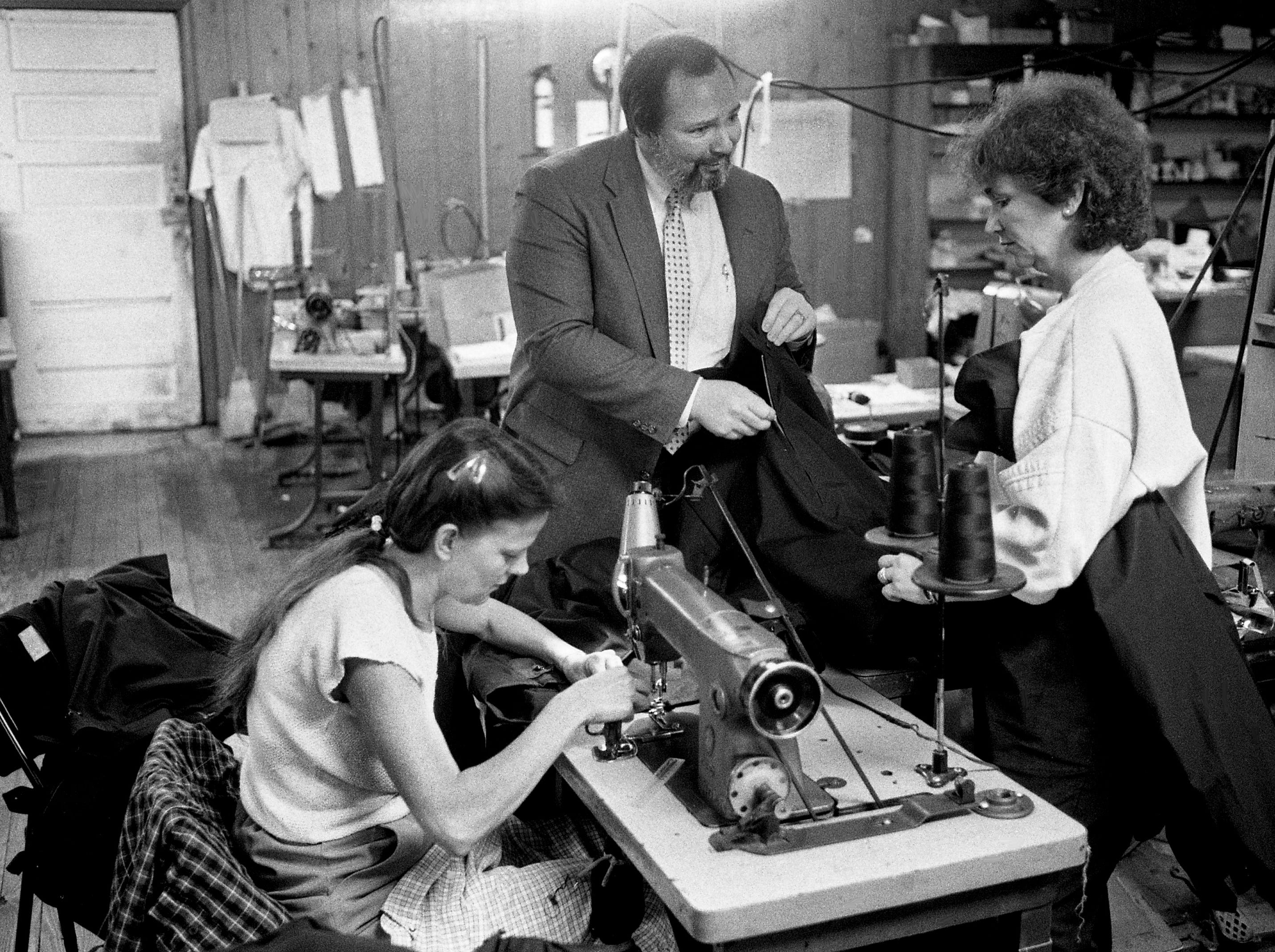 Louie Johnson, center, president of Custom Creations of Nashville, and Joanne Green, right, examine a zipper on a uniform jacket for the Navy as Susie O'Neal works on her machine at the company's plant in Westmoreland, Tenn., on Feb. 3, 1989.