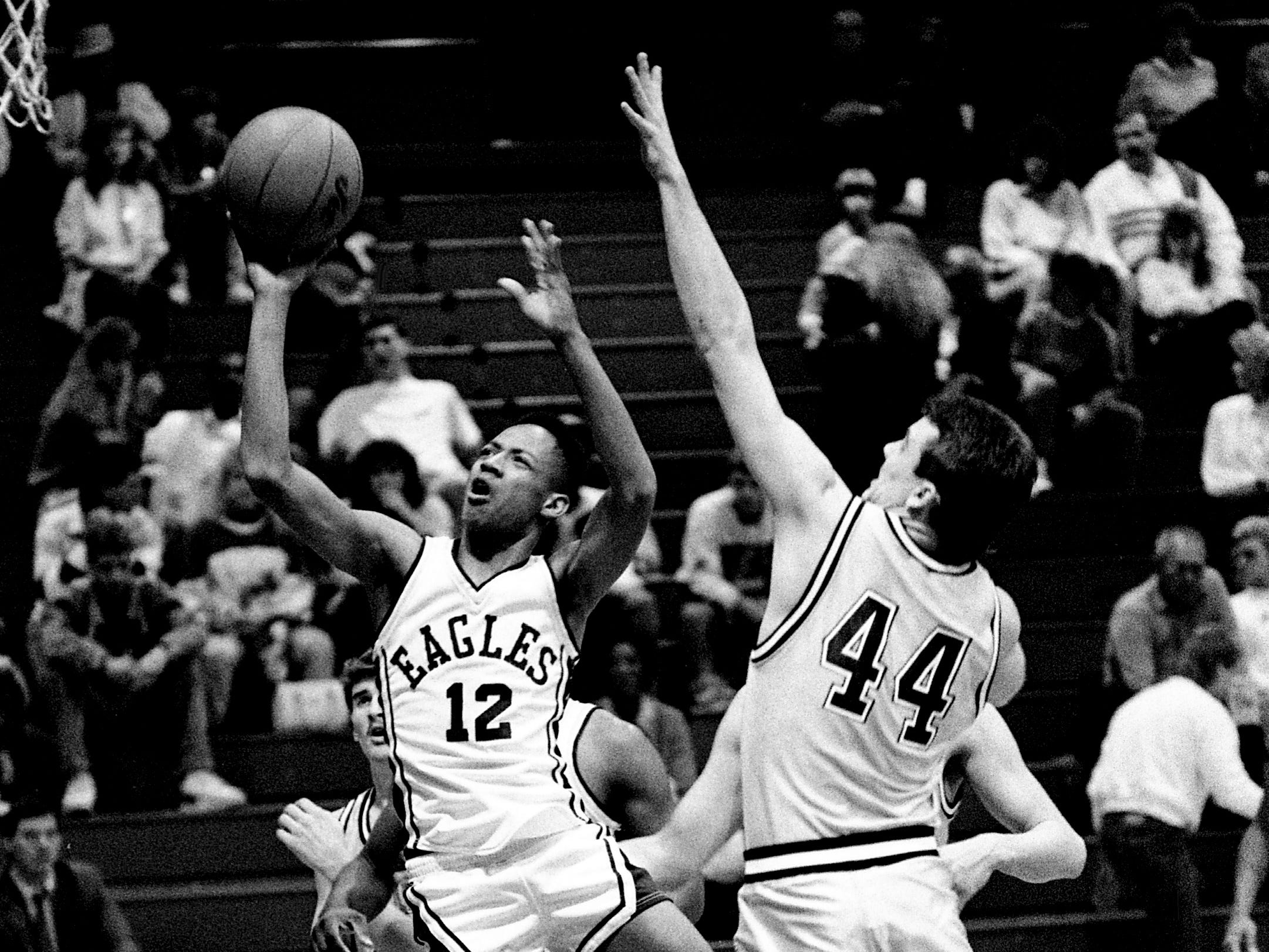 Clarksville Northeast High's Corey Parks (12) slips by Mt. Juliet High's Joby Homesley (44) for two of his 15 points in Northeast's 67-55 victory in Region 5-AAA action at Gallatin High School on Feb. 28, 1989.