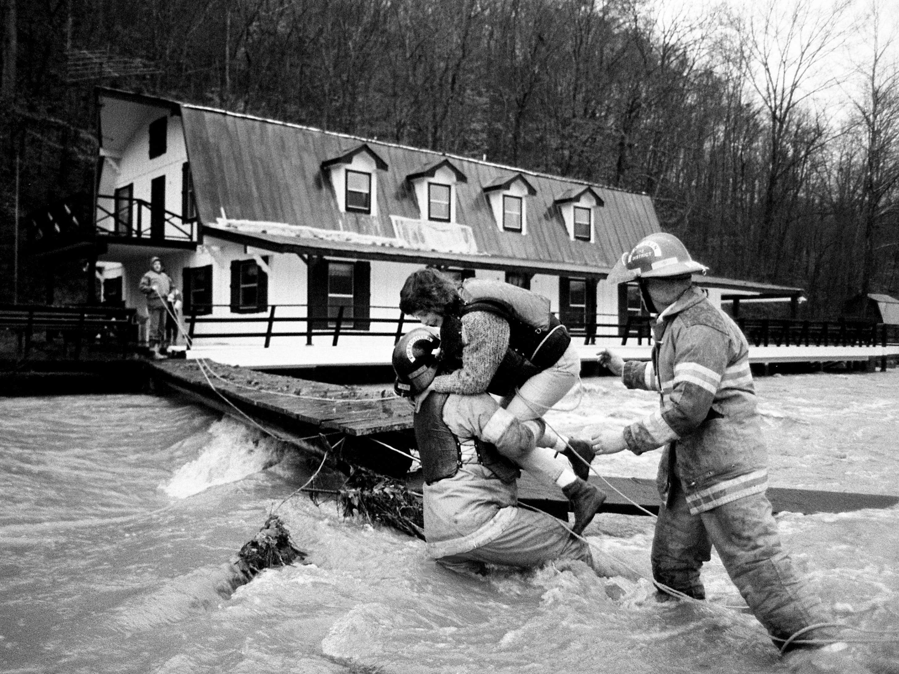 Kandi Wood, center, is rescued by Tim Hood, left, and Capt. Campbell Rice of the Williamson County Rescue Squad on Feb. 14, 1989, after rising floodwaters trapper her, her husband and their 6-year-old daughter in their home on Highway 96 west of Franklin.