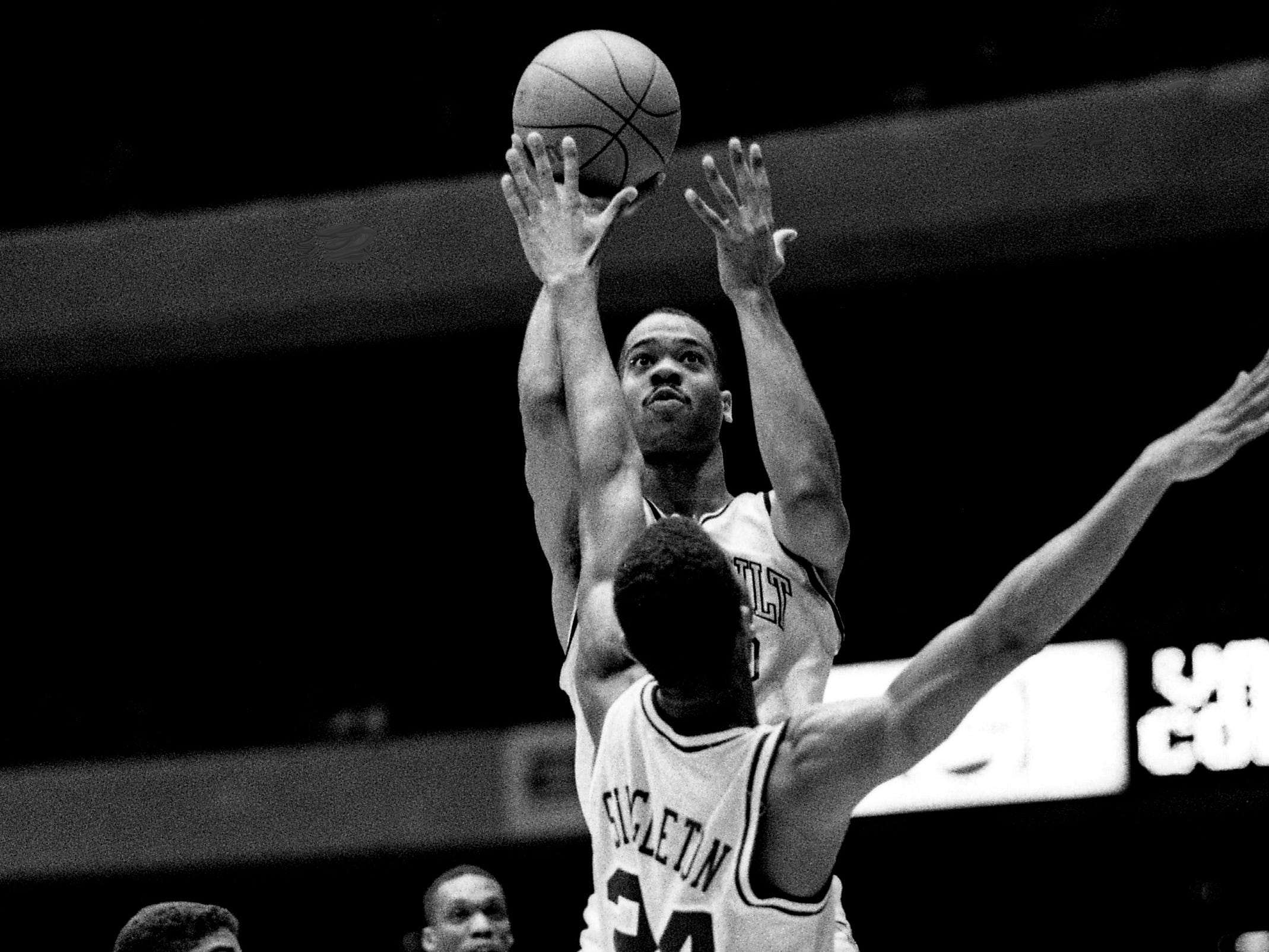 Vanderbit's Eric Reid shoots over LSU's Vernel Singleton (24) in the first half. The Commodores blew away LSU 108-74 before a deafening partisan crowd of 15,646 at Memorial Gym on Feb. 18, 1989.