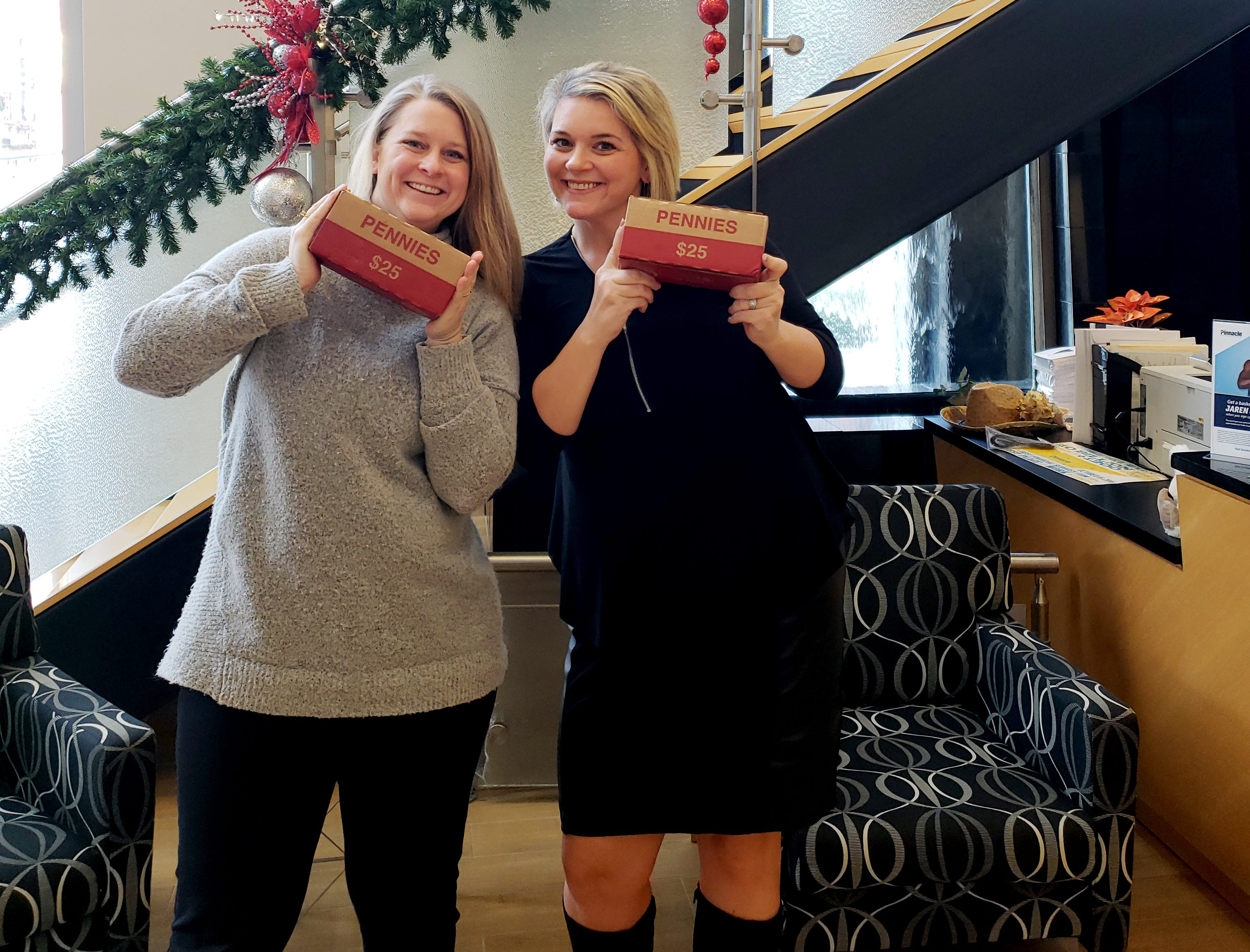 """Pinnacle Financial Partners, one of the Penny Drive sponsors, pushed their colleagues to """"buy"""" a box of pennies (aka $25)  to donate to the Penny Drive. Casey Mulligan and  Downtown Office Leader Beth Deering show off the penny boxes."""