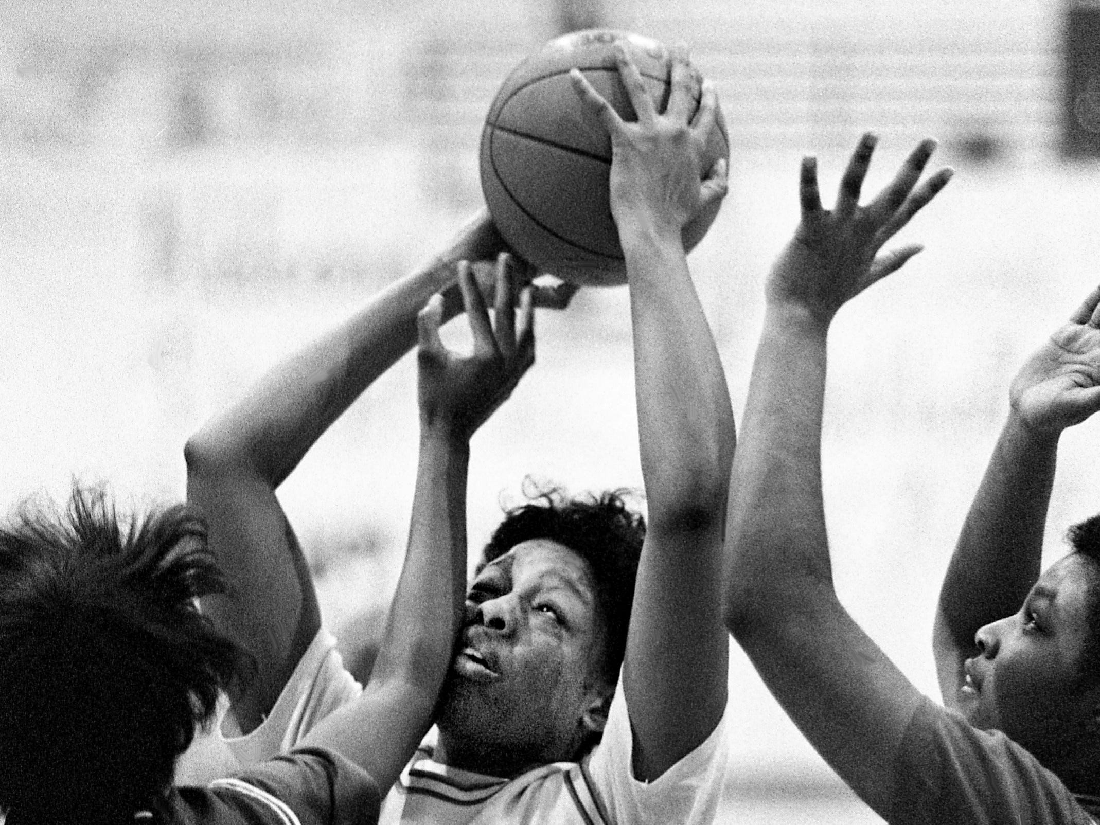 Glencliff High's Tiffany Wilson (41) squeezes between McGavock High teammates Tasha Frierson (40) and Pam Moreland en route to a 66-34 win for the District 12-AAA title at Hunters Lane High School on Feb. 24, 1989.