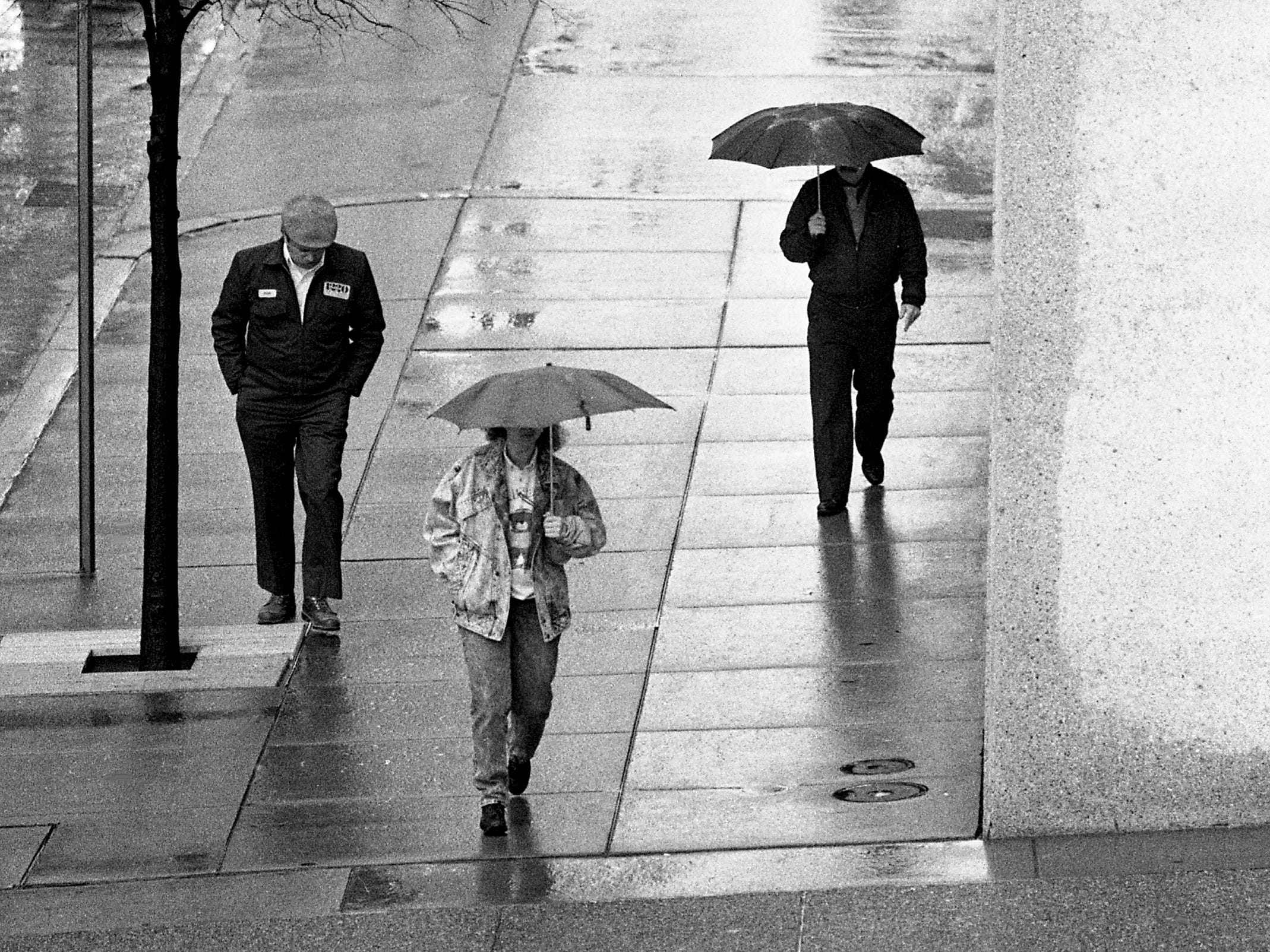 People carry umbrellas in downtown Nashville on Feb. 17, 1989. The rain was expected to turn to snow that night.