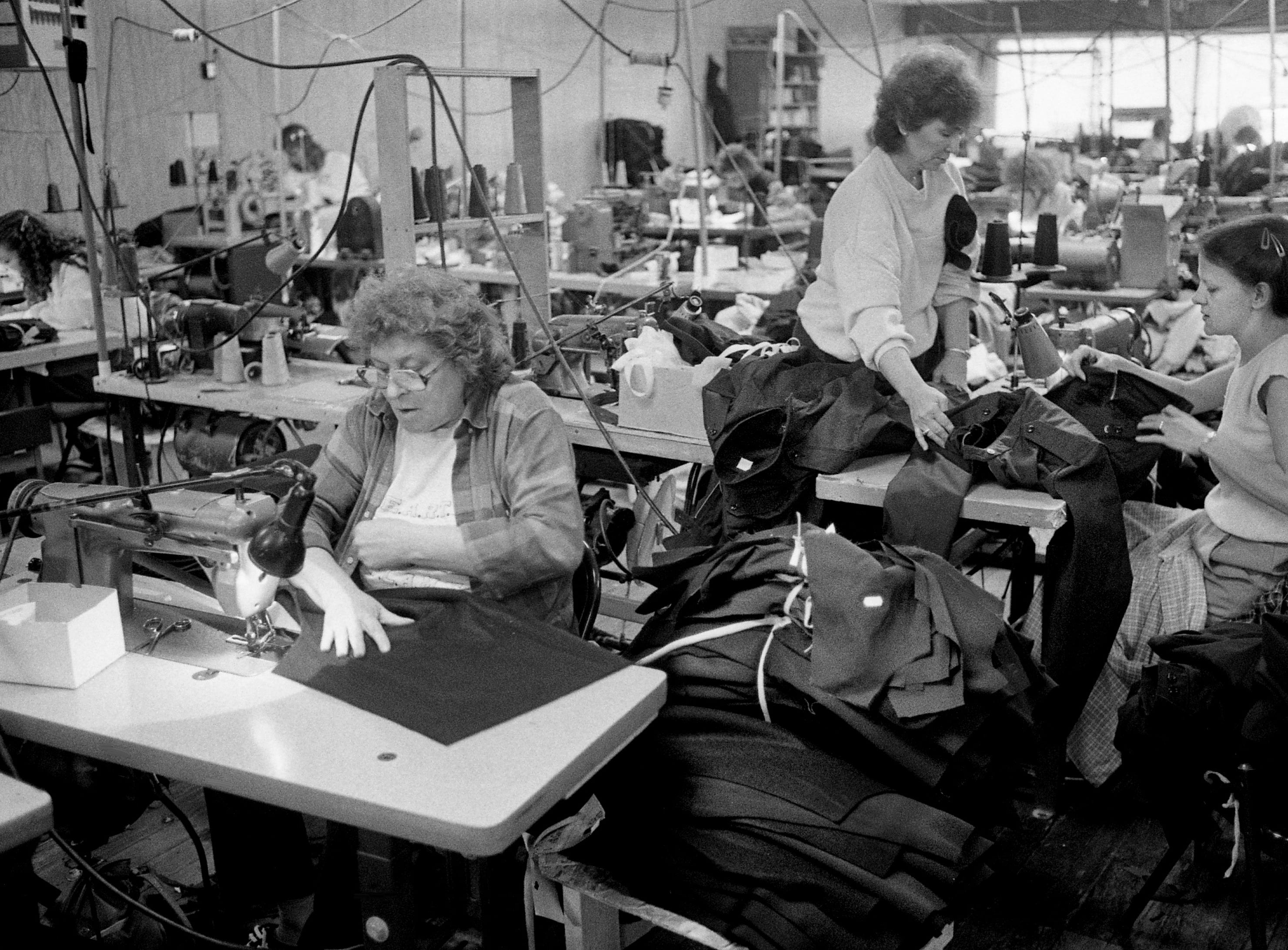 Sewing operator Corrine Sanders, left, works on a uniform jacket for the Navy as Joanne Green, standing, picks up completed garments from Susie O'Neal at the Custom Creations of Nashville plant in Westmoreland, Tenn., on Feb. 3, 1989.