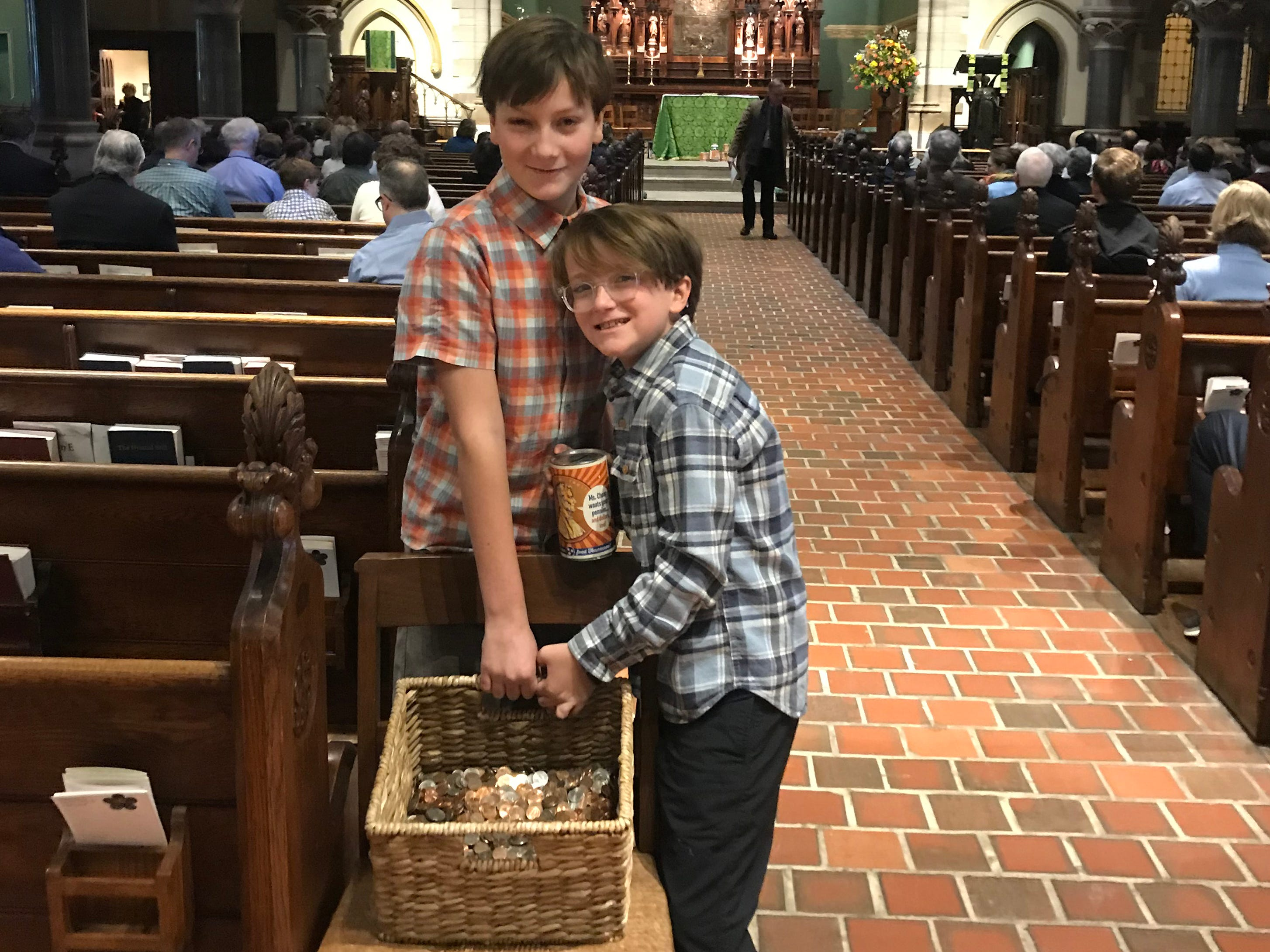 Van and Ted Williamson prepare to take some of the Penny Drive collection to the altar at Christ Church Cathedral.