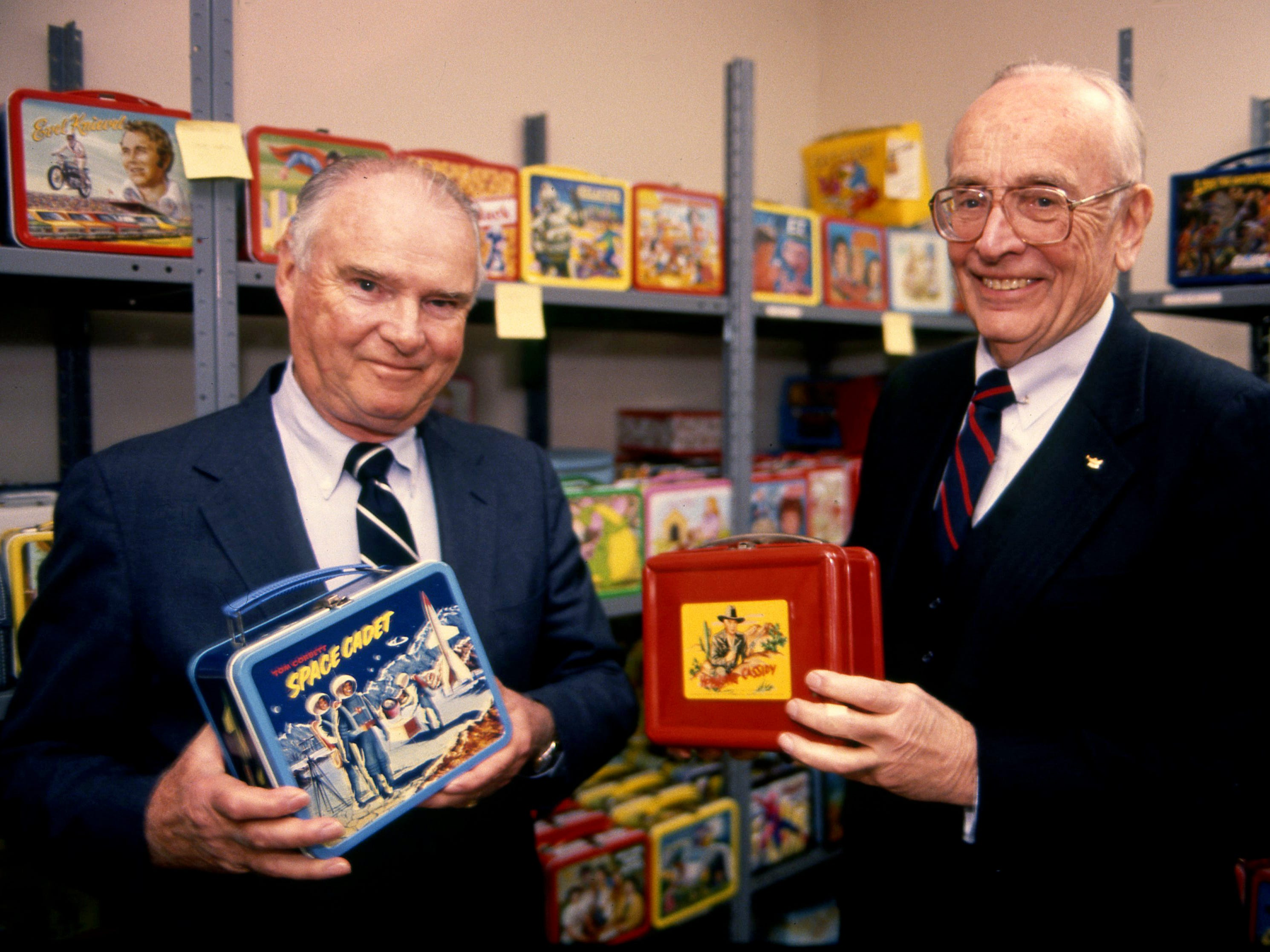 Victor Johnson Jr., right, holds a Hopalong Cassidy lunch box, which revolutionized the industry when Aladdin introduced it in 1950. George Cole displays Aladdin's second lunch box to feature a hero figure, Tom Corbett - Space Cadet.