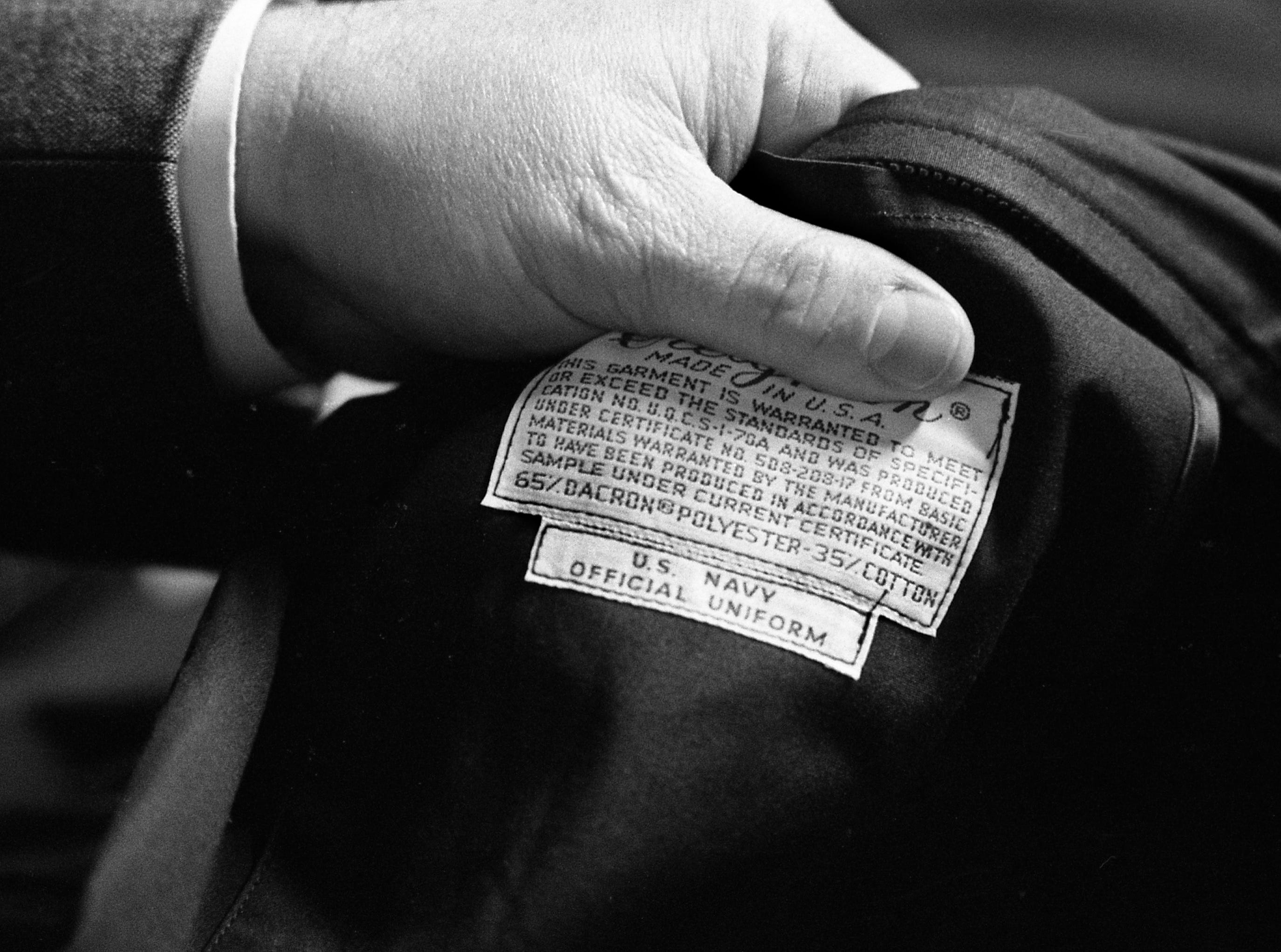 Louie Johnson, president of Custom Creations of Nashville, examines a label sewn on a uniform jacket for the Navy at the company's plant in Westmoreland, Tenn., on Feb. 3, 1989.