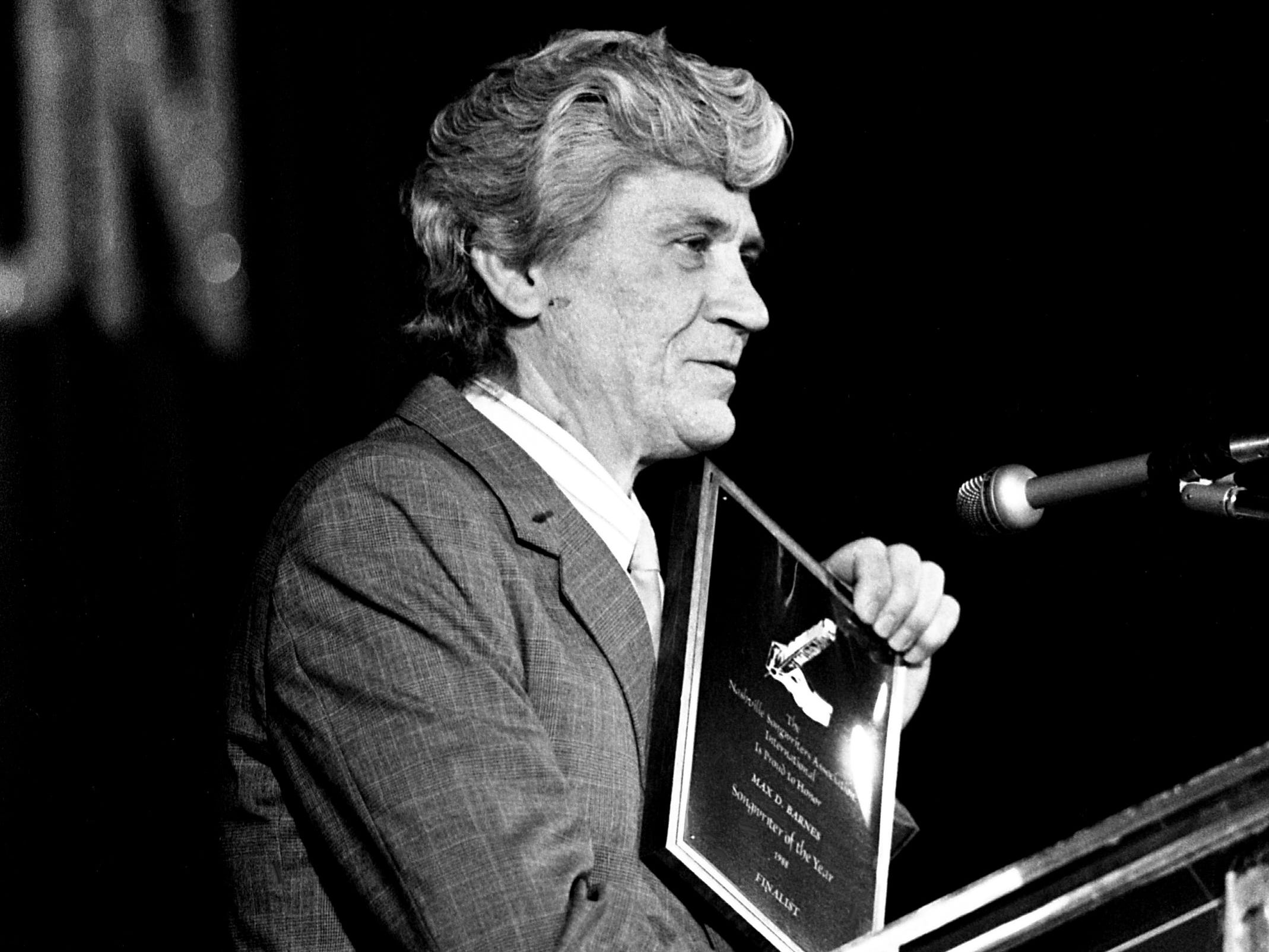 "Songwriter Max D. Barnes shows off the Song of the Year award he won for ""Chiseled in Stone"" during the Nashville Songwriters Association Songwriter Achievement Awards show at Vanderbilt Plaza on Feb. 19, 1989. The song was co-written by Vern Gosdin."