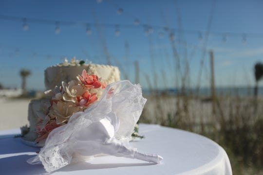 A wedding cake, really a cardboard circle with fake frosting, and shell bouquet make for great photos at a Valentine's Day ceremony at Lovers Key State Park.