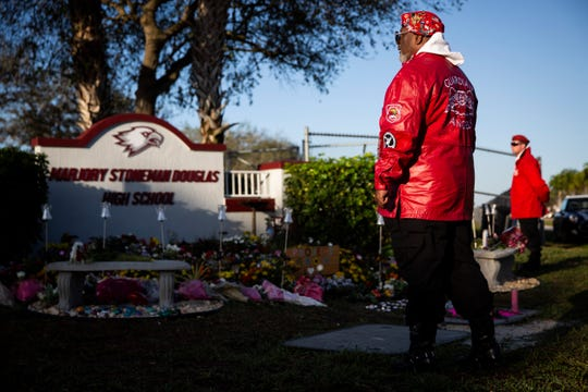 "David ""Cobra"" Clemente, left, and Mark ""Yankee"" Muniz stand guard by the memorial outside of Marjory Stoneman Douglas High School during the commemoration of the mass shooting that claimed 17 lives at the school in Parkland, Florida, on Thursday, February 14, 2019. Clemente and Muniz are part of the Guardian Angels Parkland chapter and have been standing watch at the school since the shooting last year."