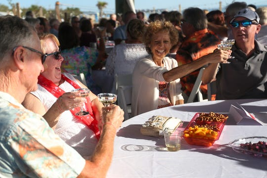 Ed and Barbara Ford, left, and Sue and John Rhoads, all from Fort Myers, enjoy champagne on the beach after renewing lifelong wedding vows at a Valentine's Day ceremony at Lovers Key State Park.