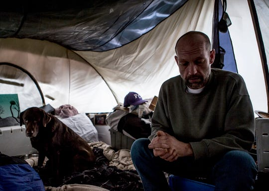 Bob and his dog, Daisy, sit in a tent they share with friends and two other dogs in Newark.