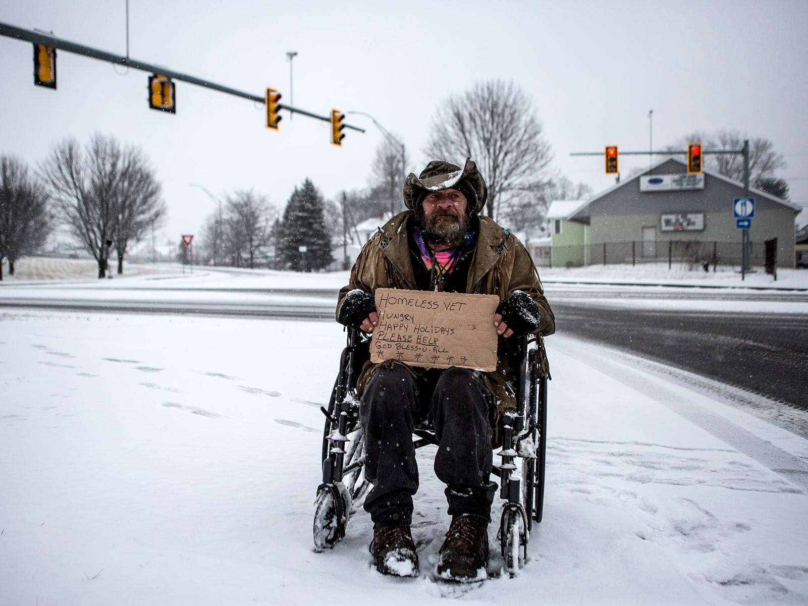 """Cowboy"" flips signs at the Cedar Street exit of Ohio 16. Cowboy who is a veteran lives in a tent in the woods. He said he lost all his money when he got sick and has been living on the streets since then."