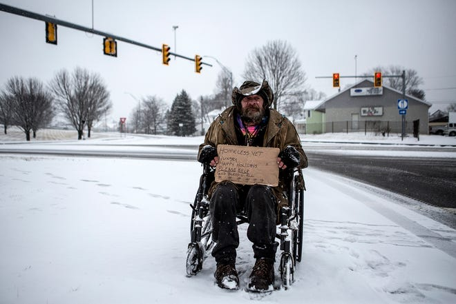 """""""Cowboy"""" flips signs at the Cedar Street exit of Ohio 16. Cowboy is a veteran who lives in a tent in the woods. He said he lost all his money when he got sick and has been living on the streets ever since."""