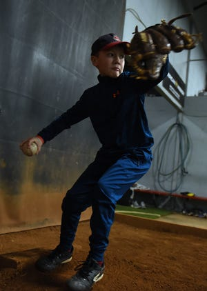 Mason Bennett, 10, practices pitching at Fearless In The Zone in Newark. Bennett, a student at Stevenson Elementary School in Heath, was born with congenital heart defects and has been through six heart surgeries, but remains active, is on all-star baseball teams and also plays other sports.