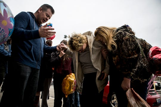 Joyce Bowman, Chastity Inman, Erika Snyder, pray with Brandon Wilson at the site where  Rodney E. Peyton was stabbed to death on Deo Drive Monday. Wilson was with Petron as he died. Family and friends gathered at the spot where he was killed to release balloons, February 14, which would have been his 39th birthday.