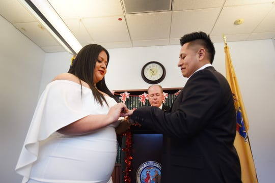 Yesenia Urgiles and Cesar Guartan of Hackensack, exchange their wedding rings before Bergen County Clerk John S. Hogan during their wedding ceremony, located at Bergen County Plaza in Hackensack on 02/14/19.