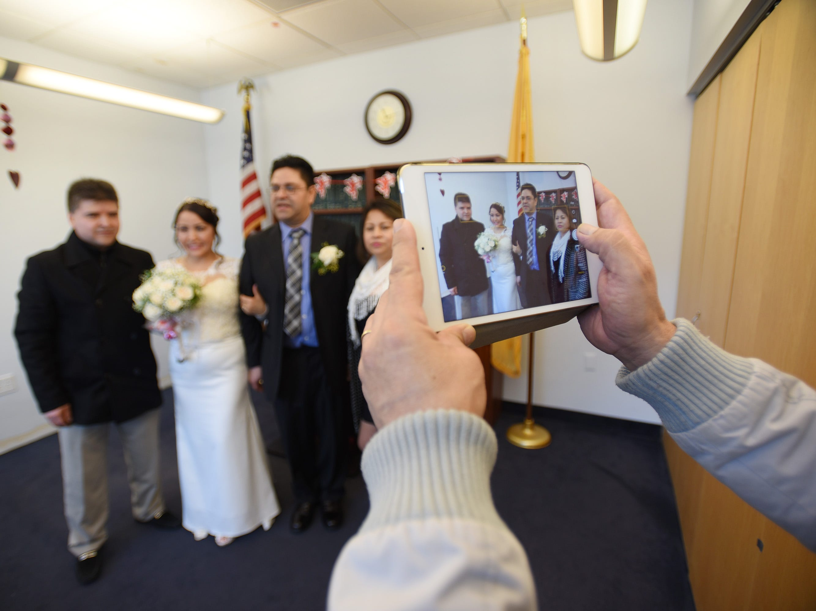 After being announced as a husband and a wide, Gloria Gallego and Alexander Gutierrez of Englewood, have photos taken together with members of their family following their wedding ceremony, located at Bergen County Plaza in Hackensack on 02/14/19.