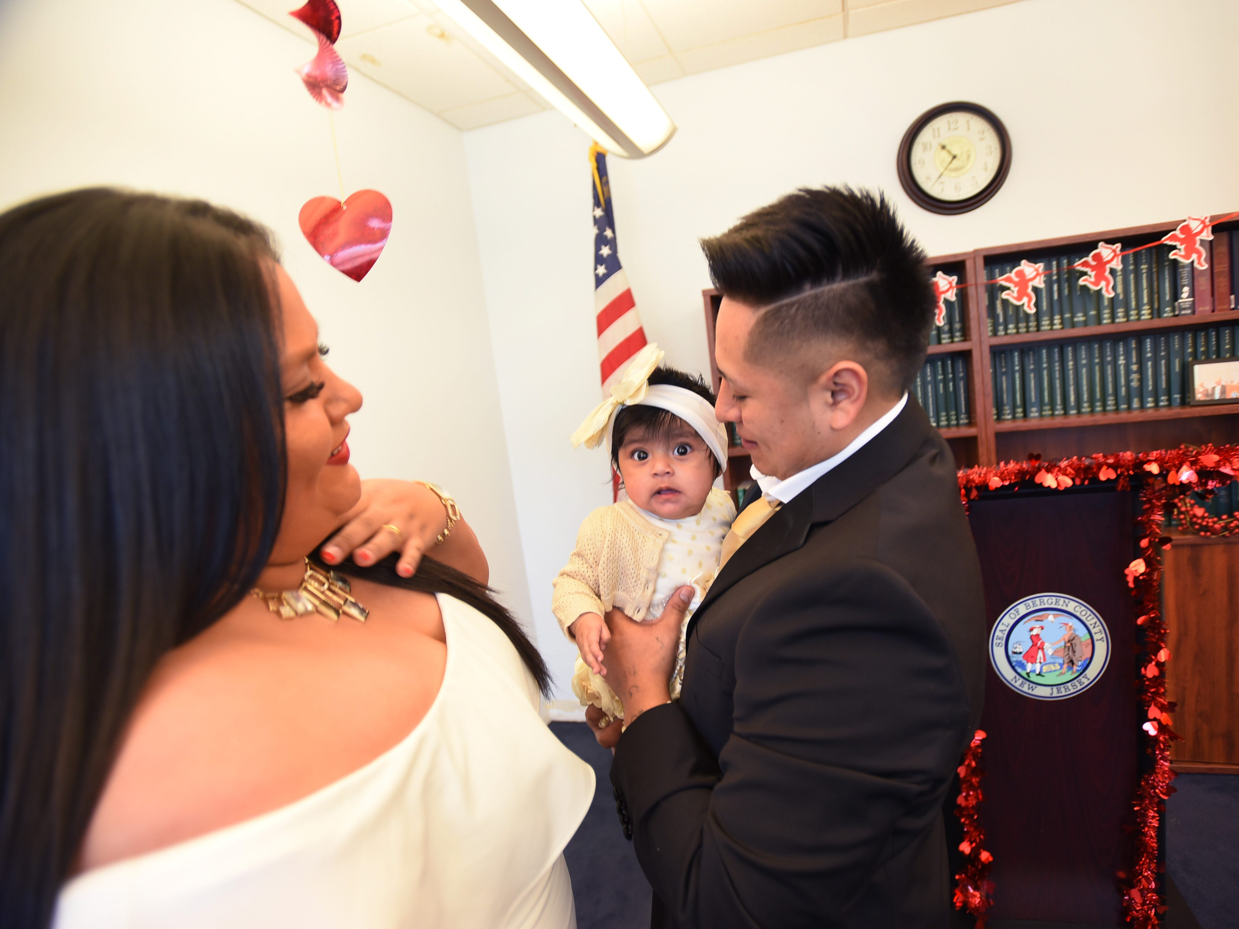 After being announced as a husband and a wife, Yesenia Urgiles and Cesar Guartan of Hackensack, look at their five month daughter Lilian following their wedding ceremony, located at Bergen County Plaza in Hackensack on 02/14/19.