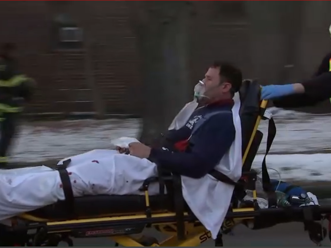 A person is wheeled out on a stretcher as firefighters battle a blaze in Fort Lee on Thursday.