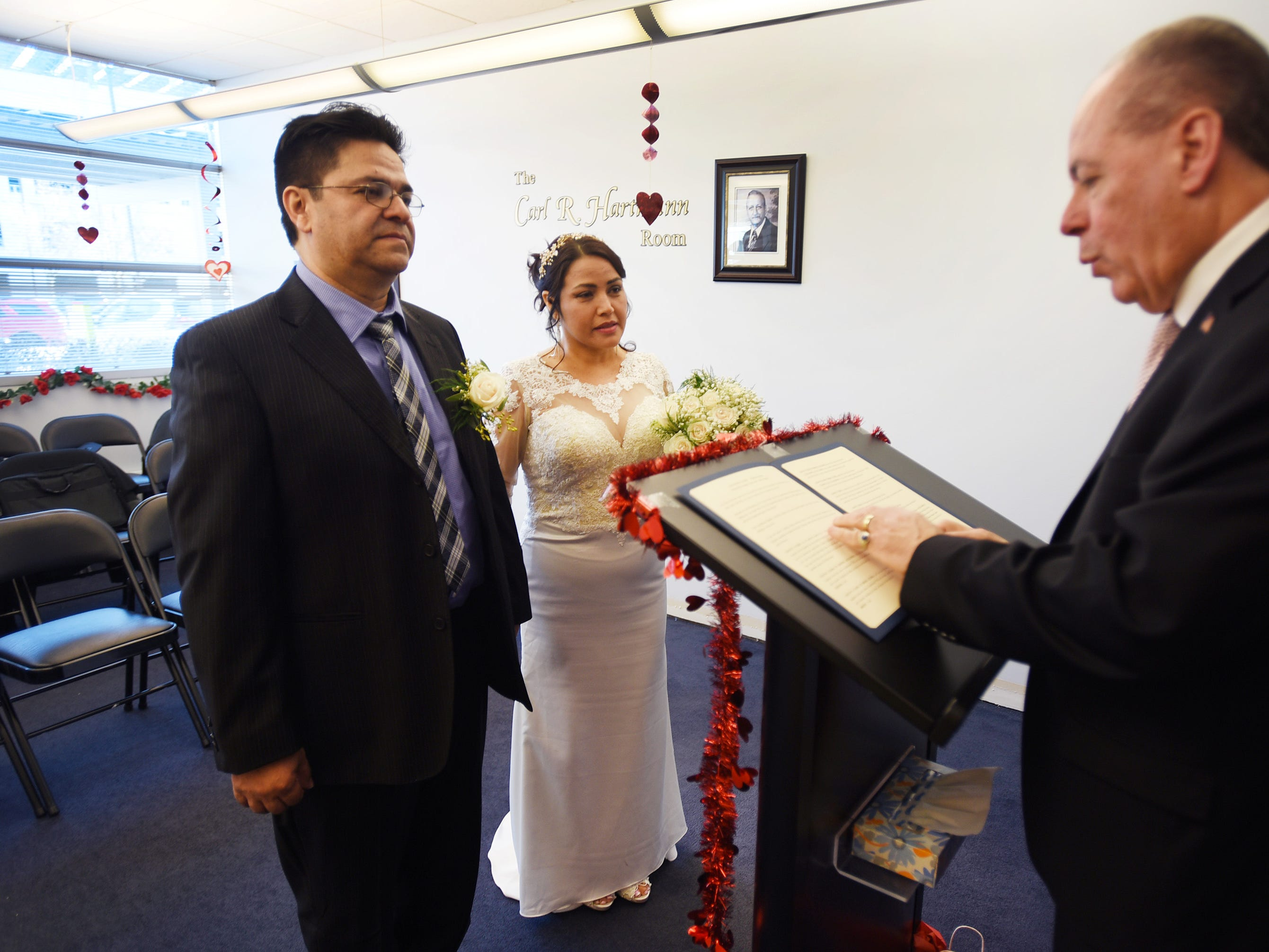 Bride and groom, Gloria Gallego and Alexander Gutierrez of Englewood, stand before Bergen County Clerk John S. Hogan during their wedding ceremony, located at Bergen County Plaza in Hackensack on 02/14/19.