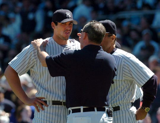 Yankees trainer Gene Monahan checking pitcher Carl Pavano after he was hit in the head by a ball hit by the Orioles Melvin Mora.