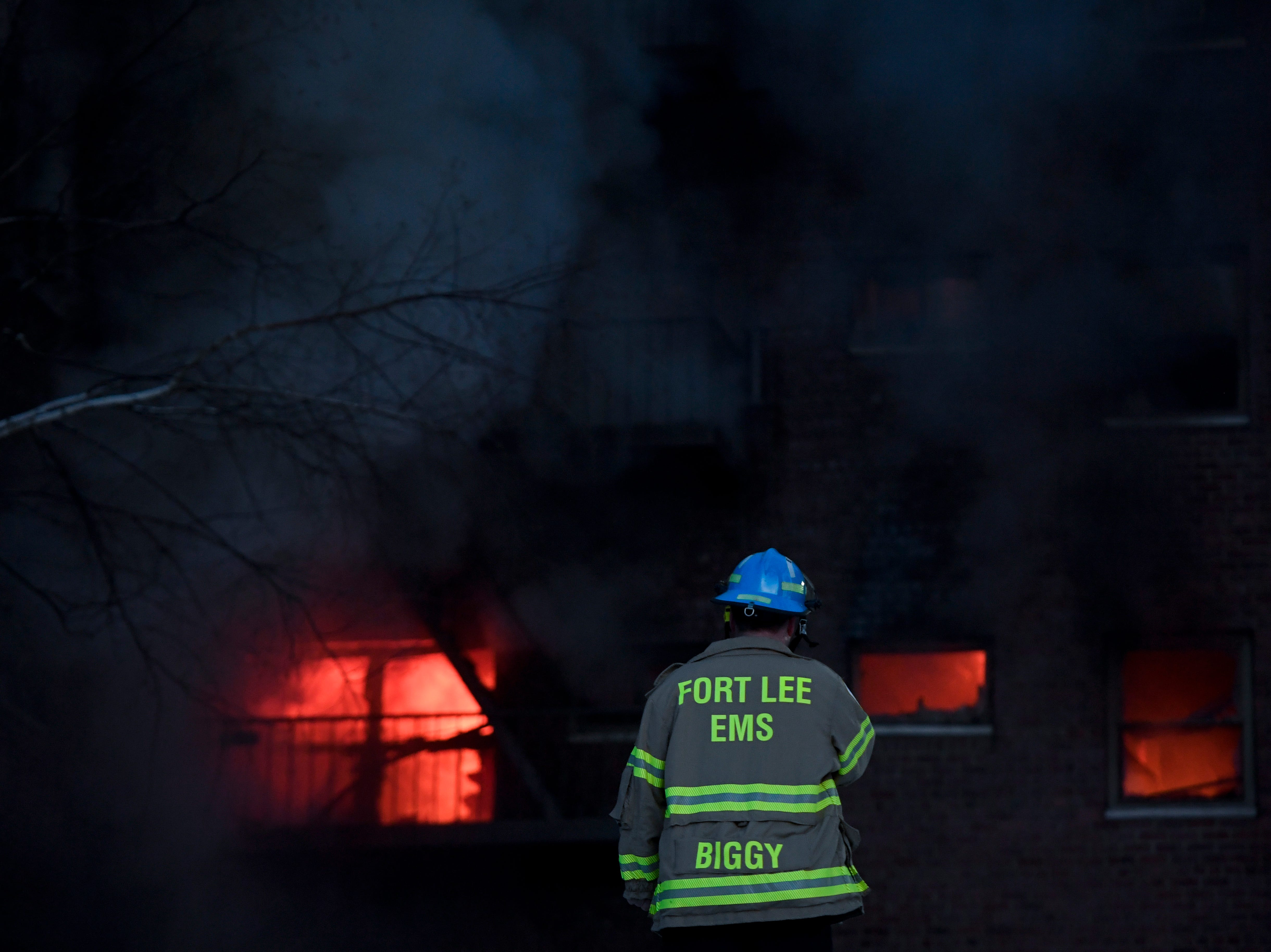 A Fort Lee EMT looks on as a fire rages within an apartment building on Edwin avenue in Fort Lee on Thursday, Feb. 14, 2019.